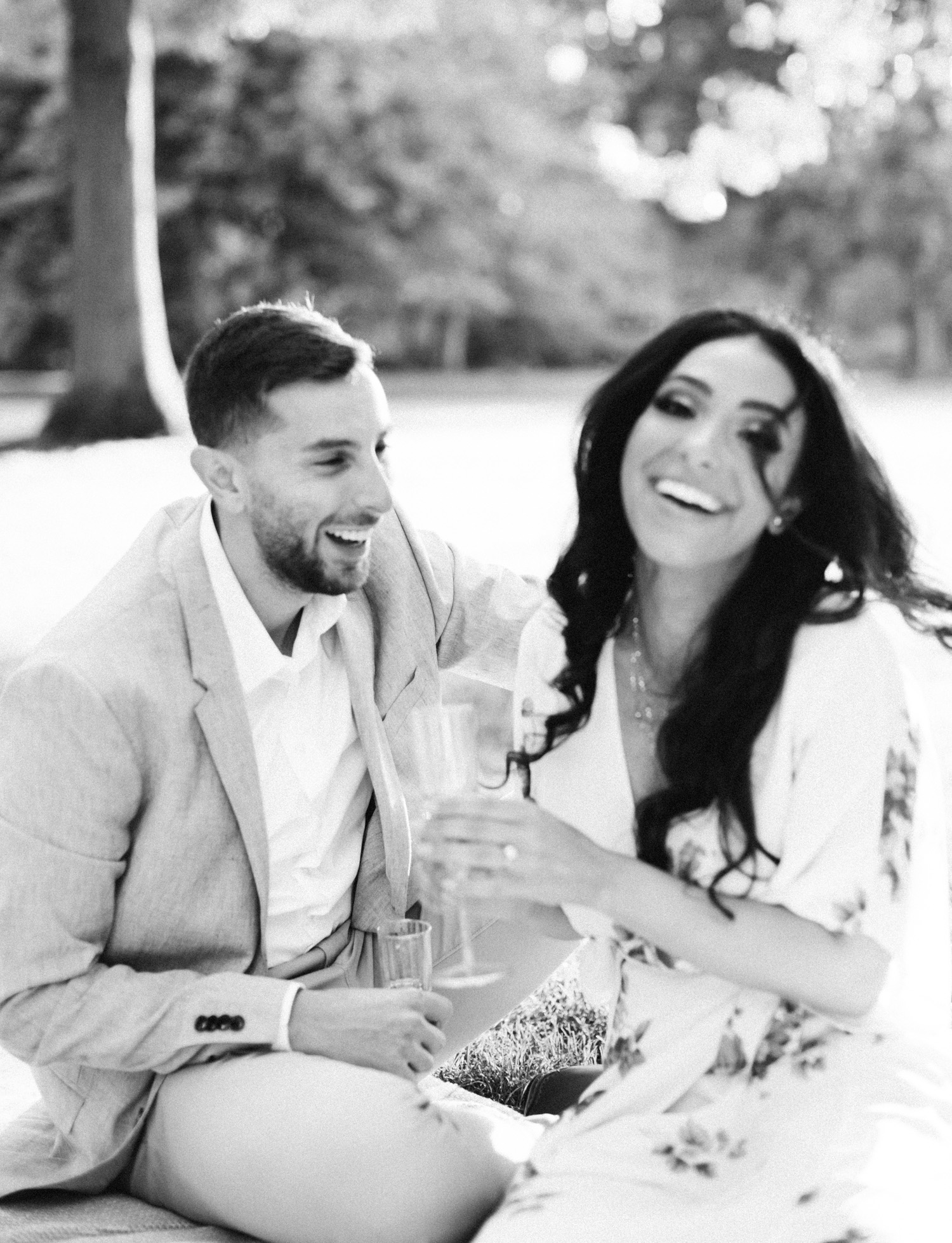 A soft black and white film photo of an Arab couple laughing during their natural engagement session in Detroit