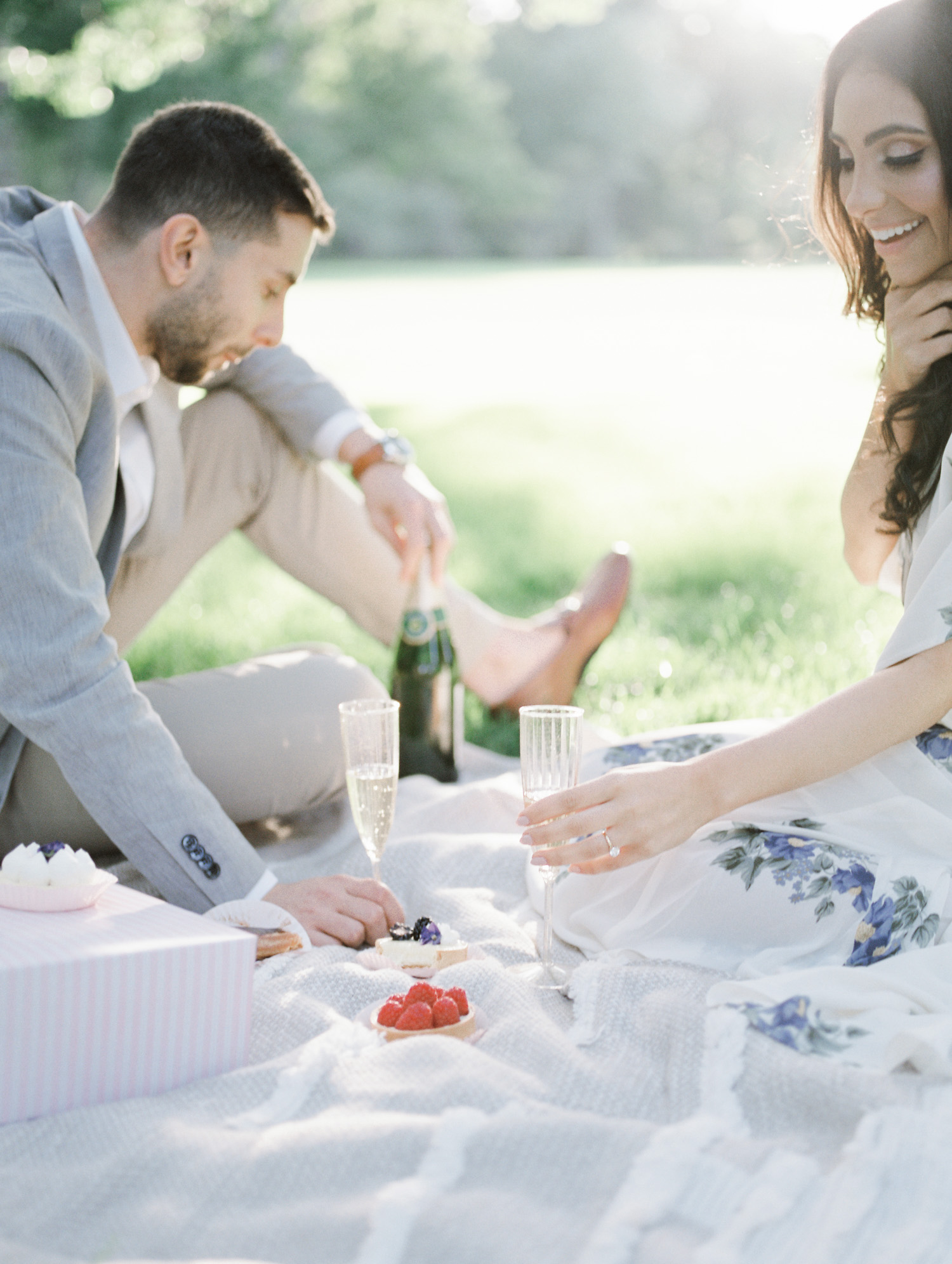 Champagne and fruit tarts rest on a picnic blanket with a couple during their film engagement photos in Michigan