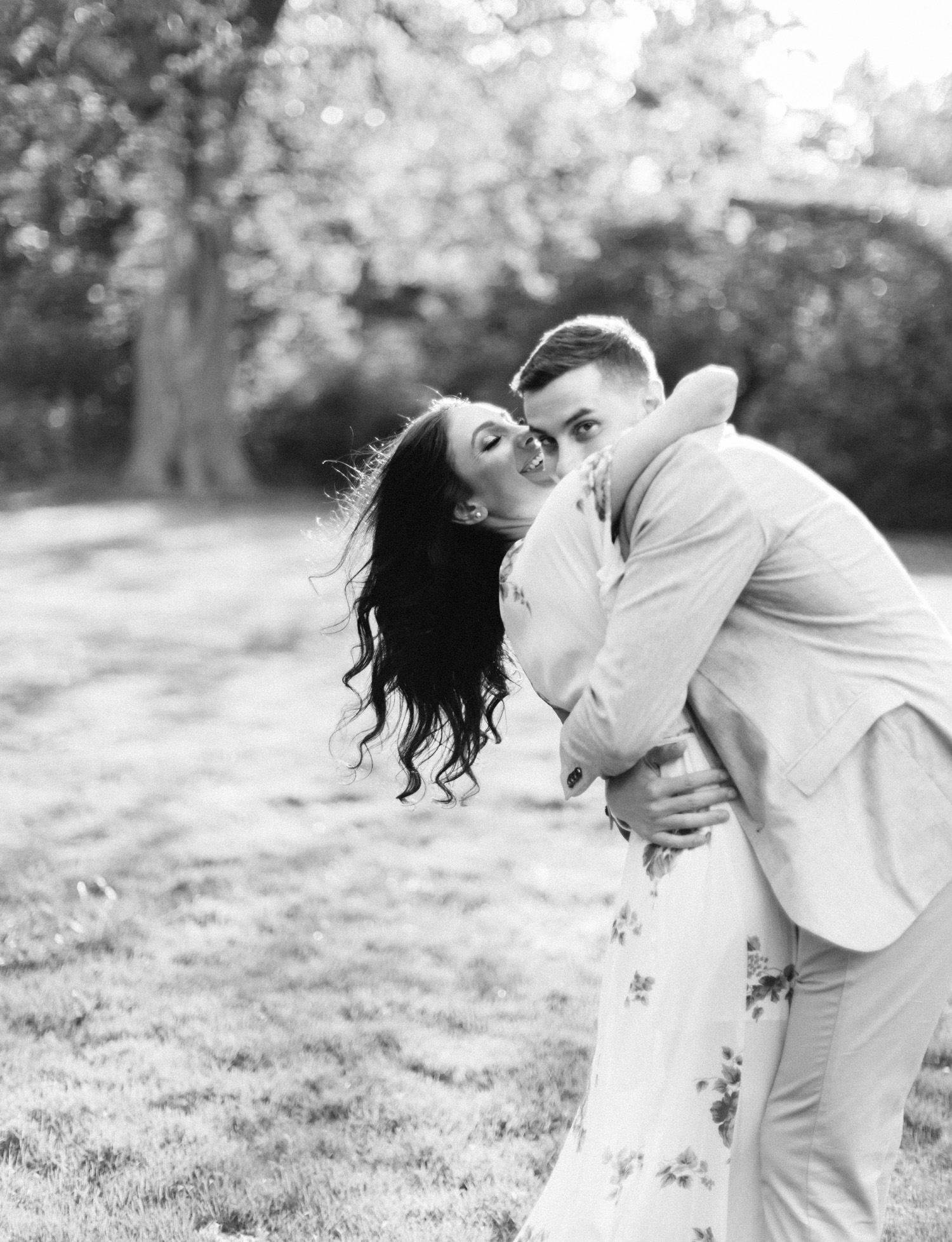 a laughing couple hugs during their engagement photo shoot at the Ford House in Michigan