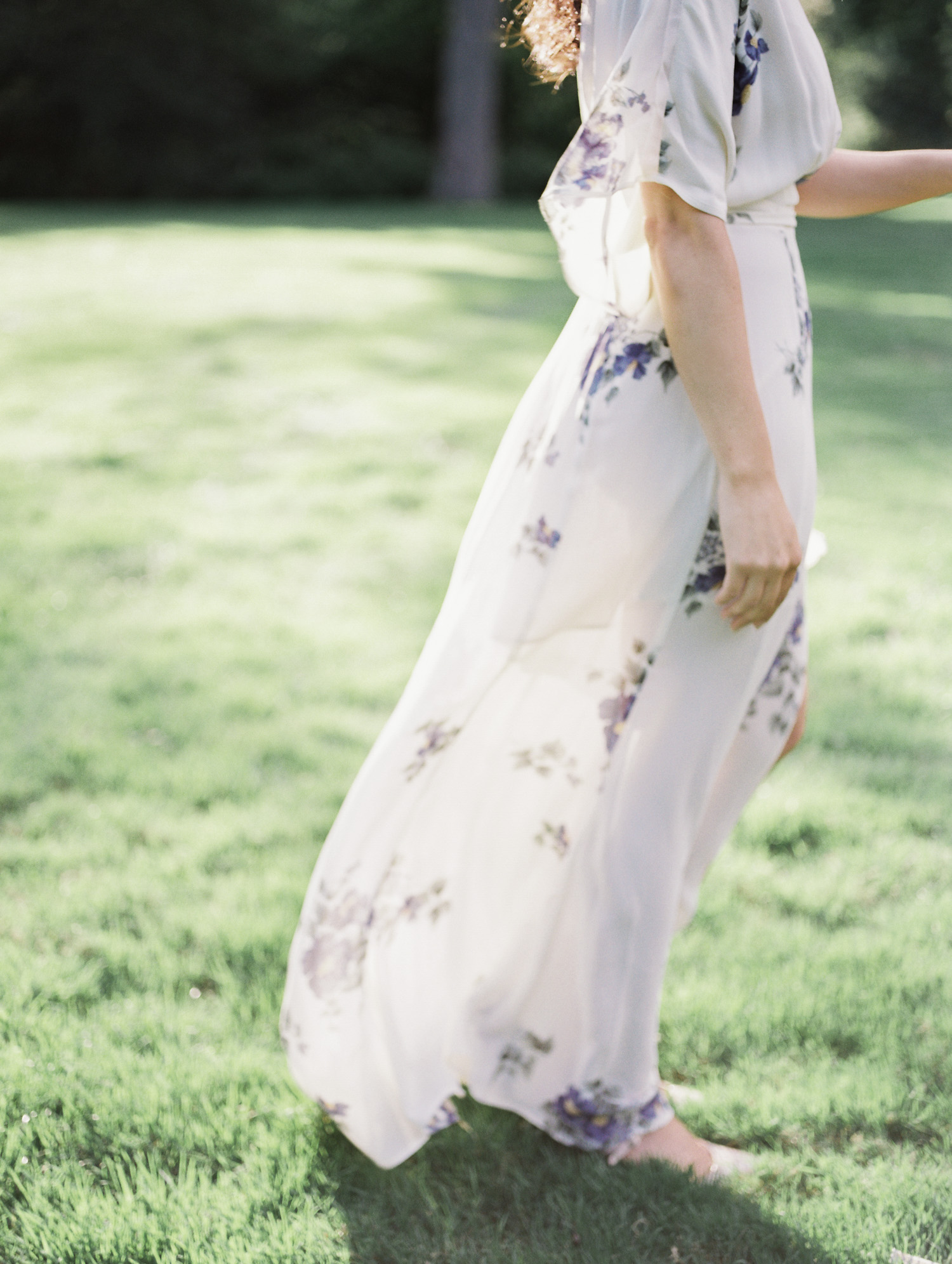 a woman's engagement photo outfit, a long white dress blows in the wind at the Edsel & Eleanor Ford House