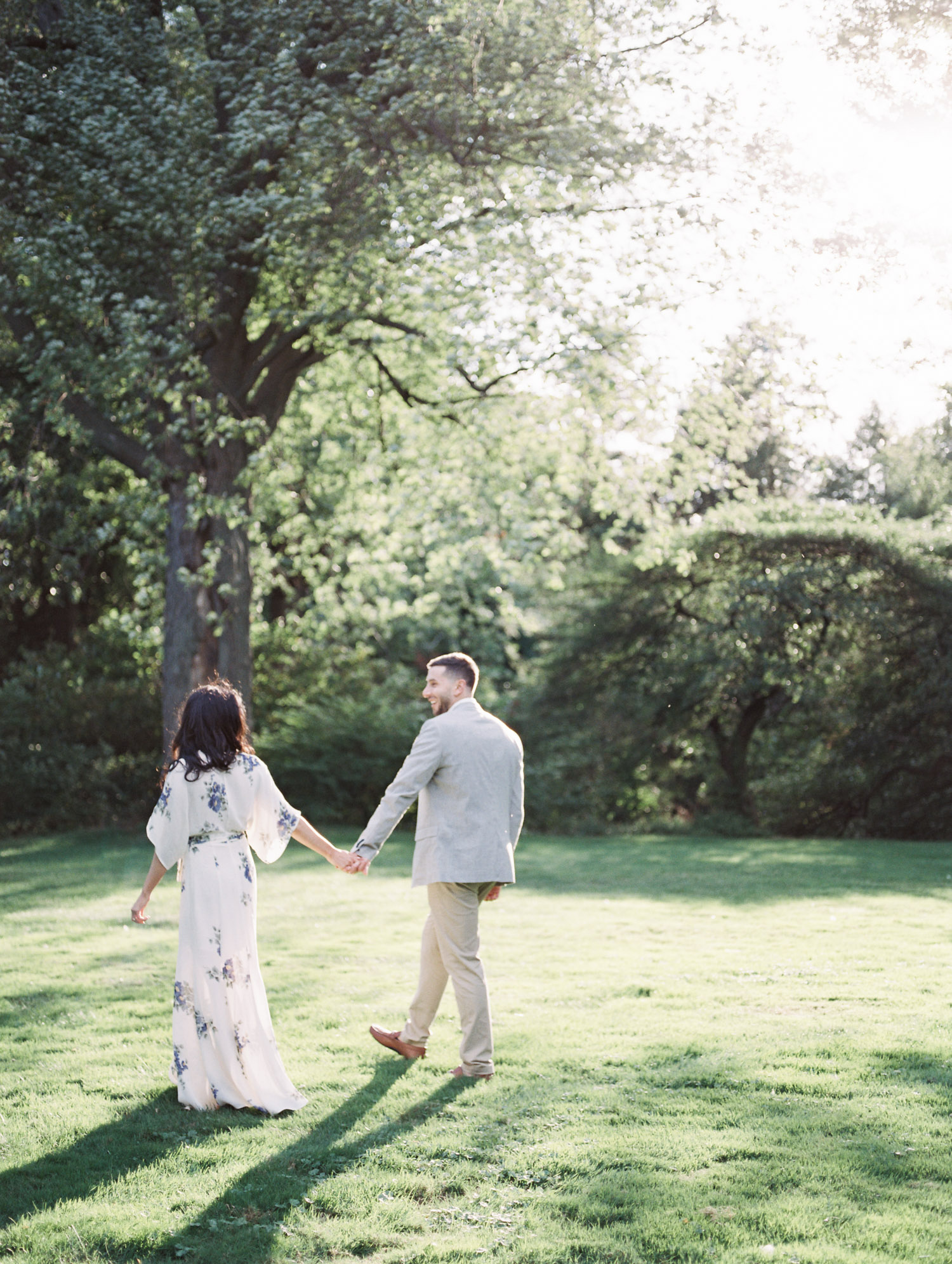 A couple holds hands while walking in luminous light at the Edsel & Eleanor Ford House during their film engagement photos in Michigan