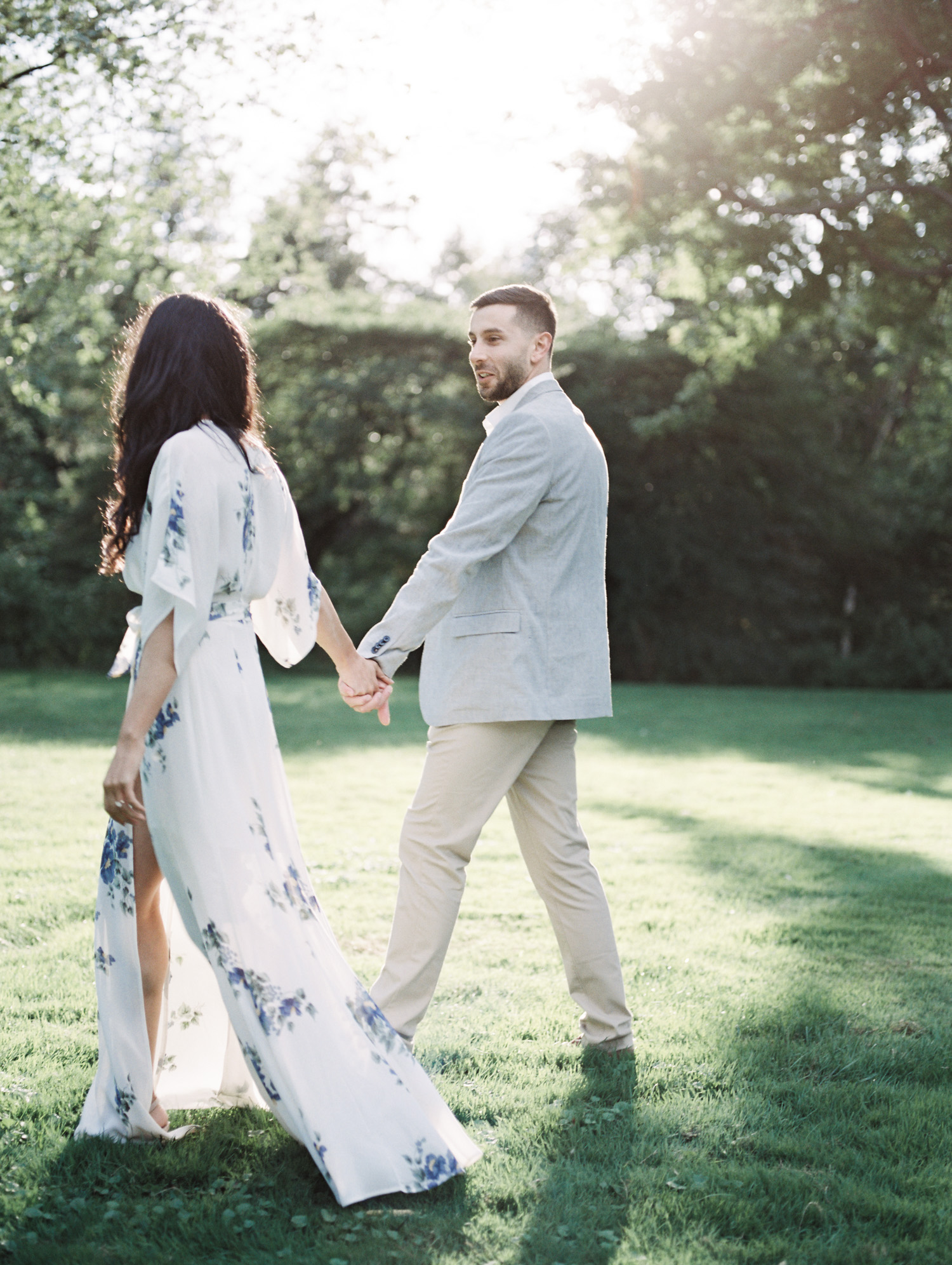 An Arab couple holds hands walking in luminous light at the Ford House during their film engagement photos