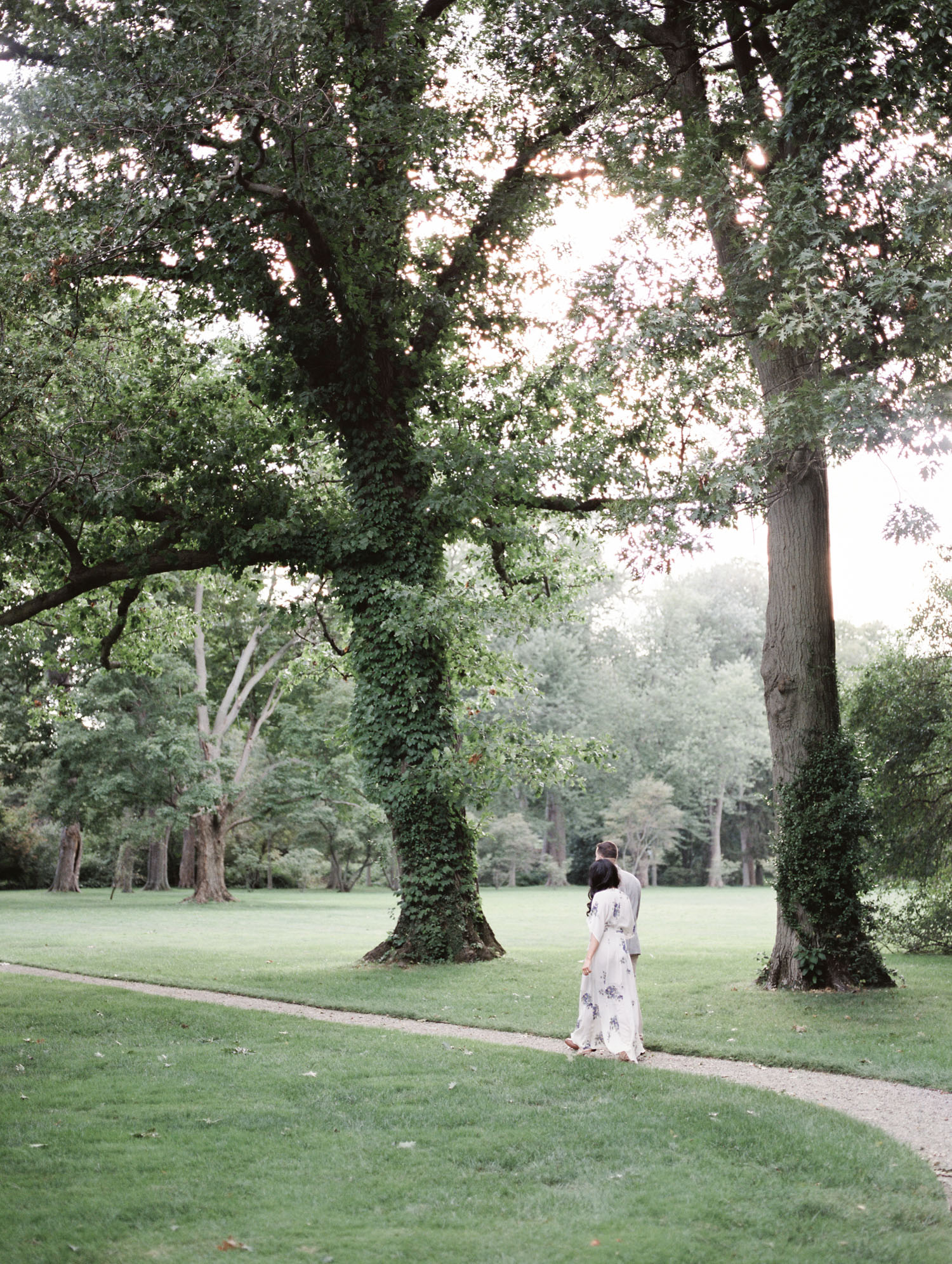An Arab couple walks among big old trees during their film engagement photos at the Ford House in Michigan
