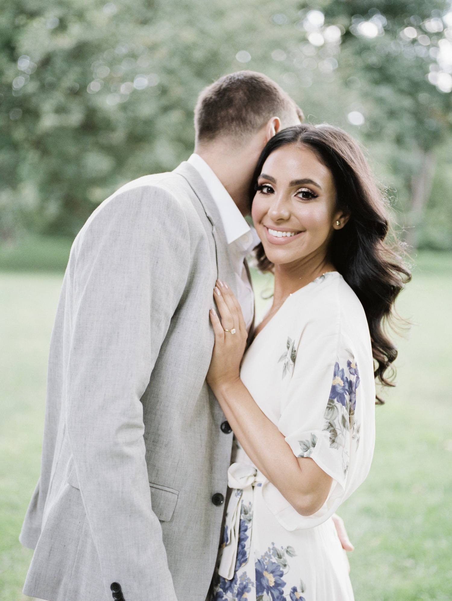 A beautiful Arab woman smiles while embracing her man during their film engagement photos at the Ford House in Detroit, Michigan