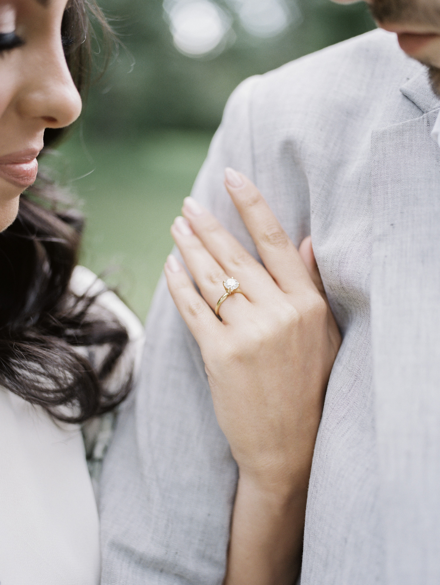A woman's solitaire diamond engagement ring is seen close-up as she holds her man's arm during their engagement photos on film in Michigan