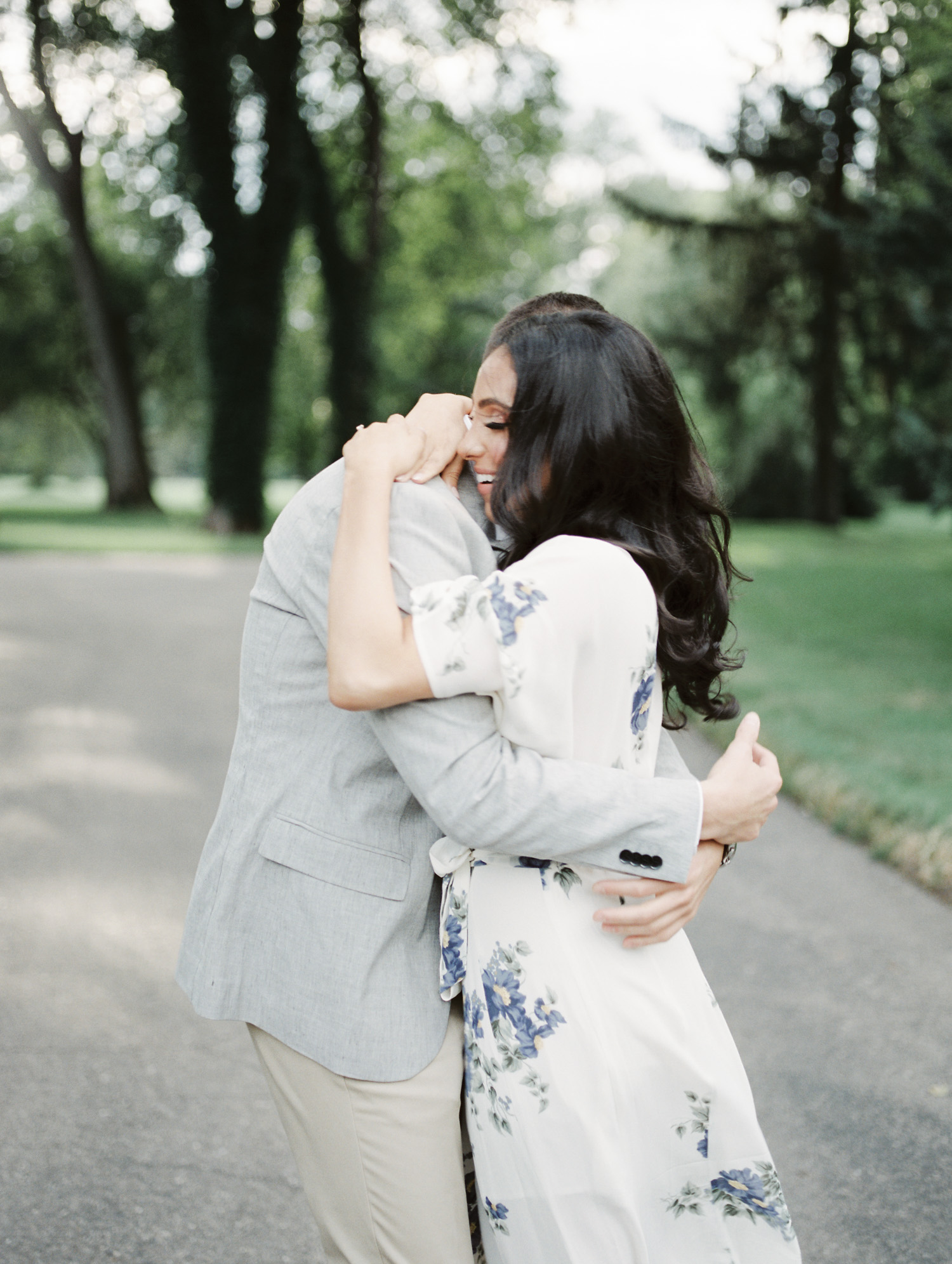 a laughing couple embraces during their engagement photos in Grosse Pointe Shores, Michigan