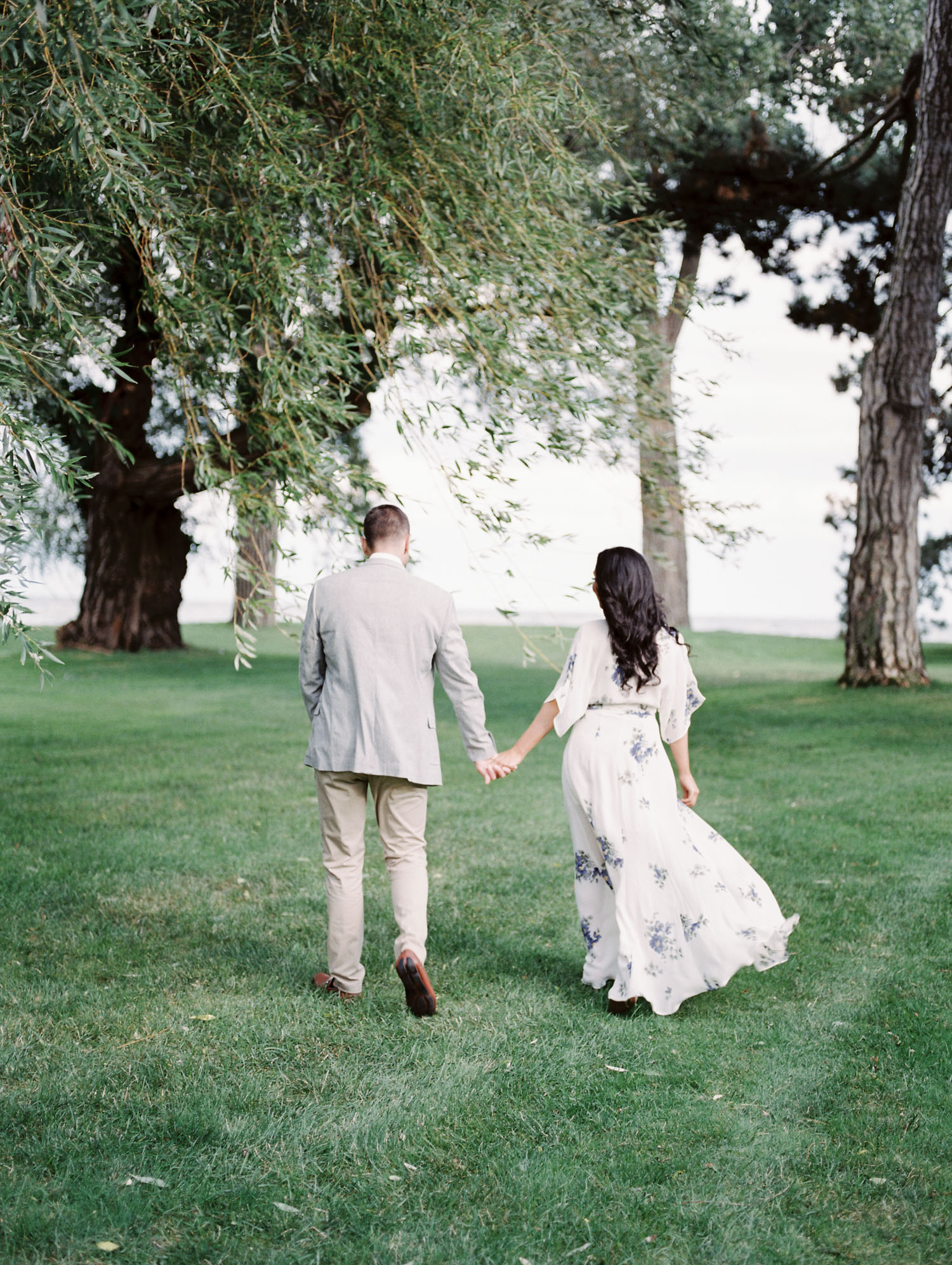 A couple walks under windswept weeping willow branches by the lake during their film engagement photos at the Ford House in Michigan