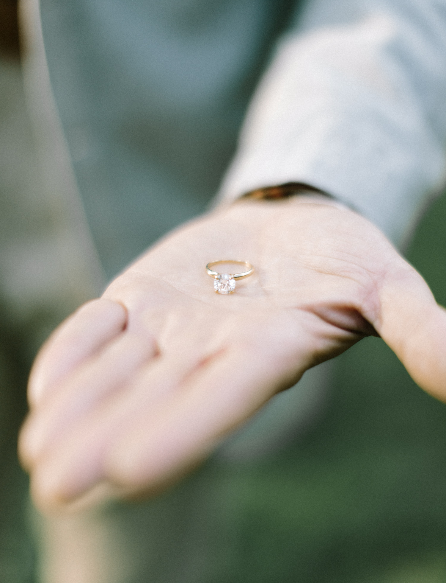 a solitaire round diamond engagement ring in yellow gold rests in a man's palm during engagement photography in Southeast Michigan