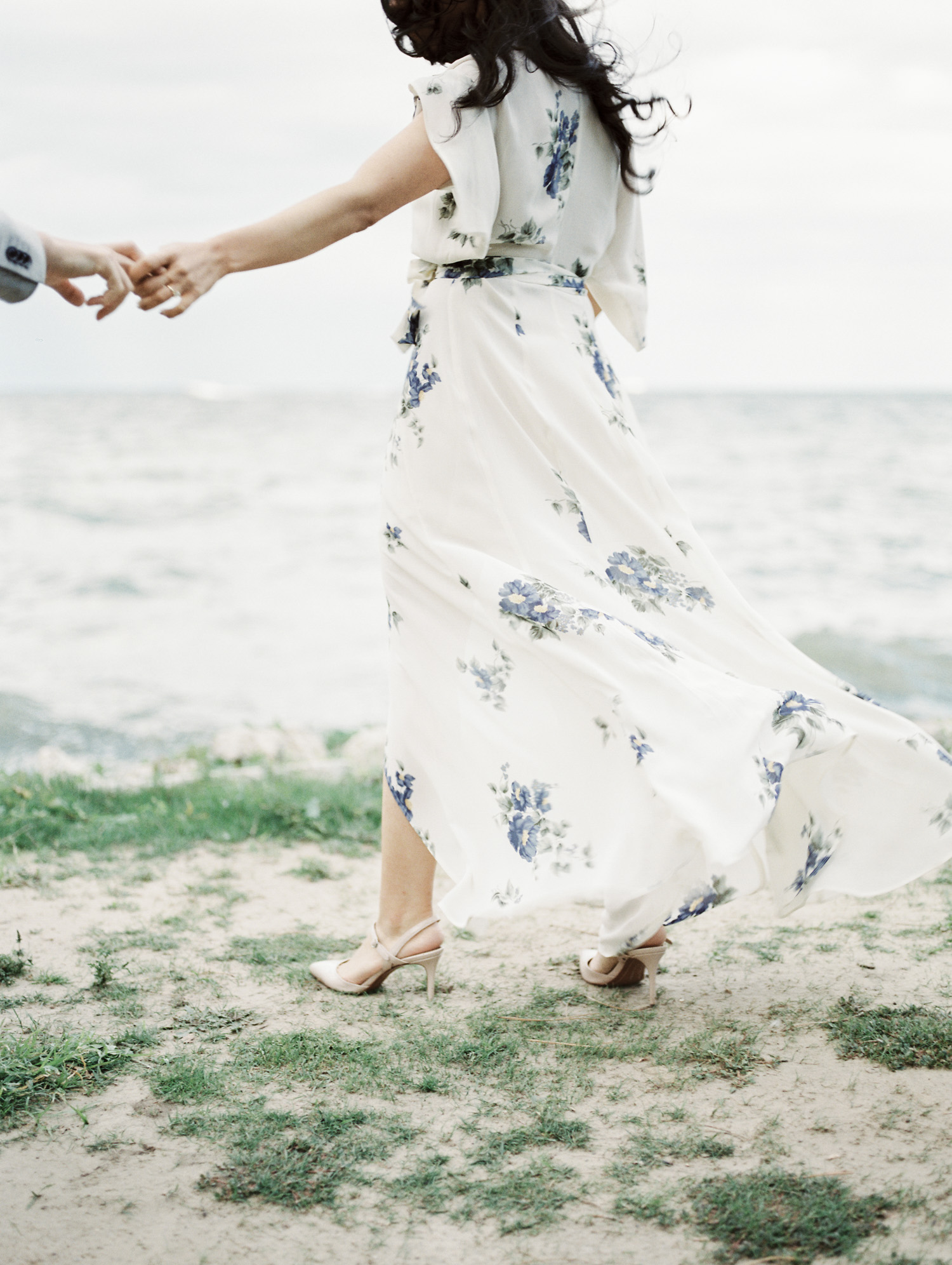 A woman's stylish engagement session outfit, a white floral print maxi dress, blows in the wind by the lake during a film engagement photo shoot