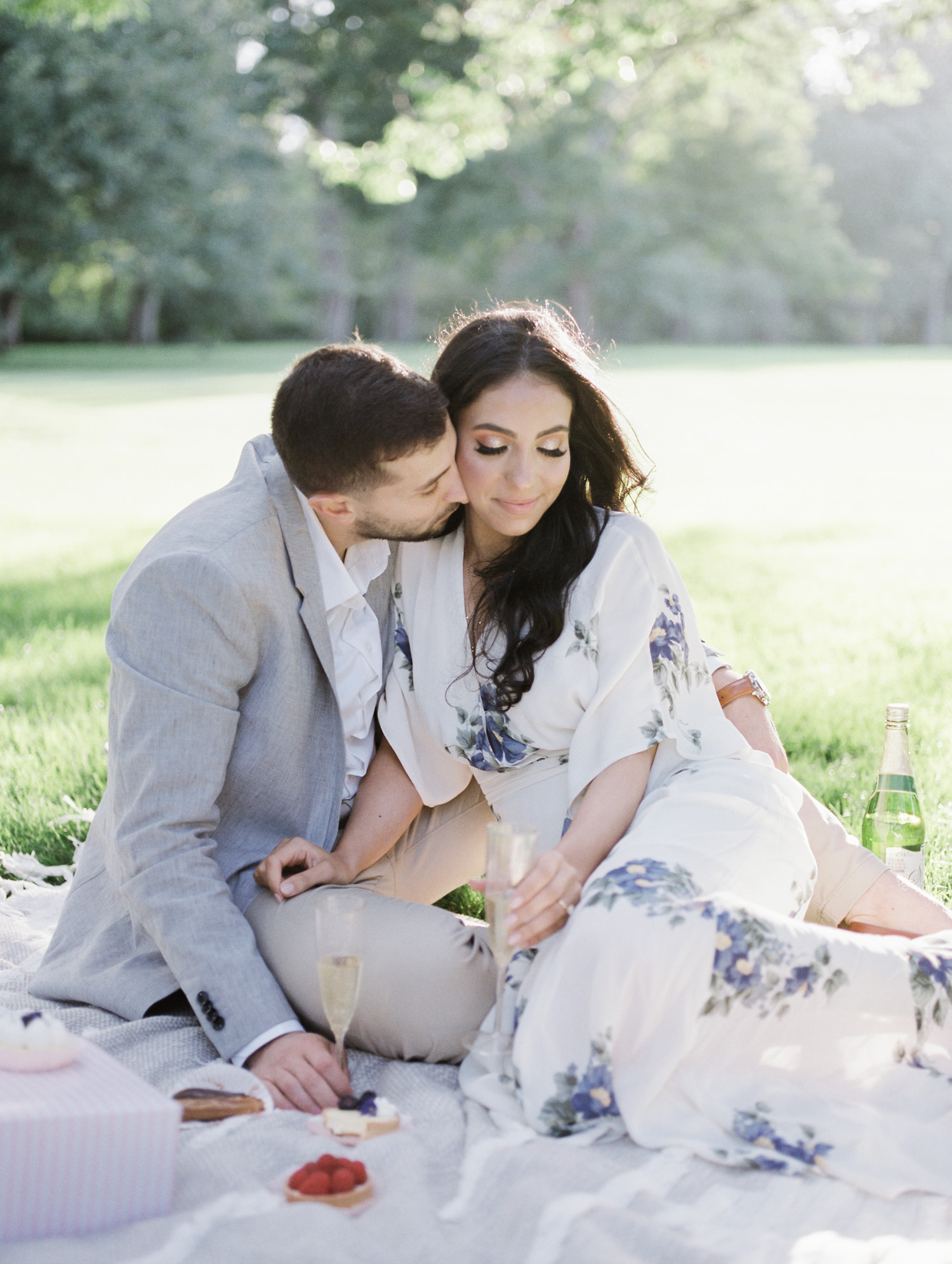 An Arab couple cuddles on a blanket during their picnic engagement photos at the Ford House