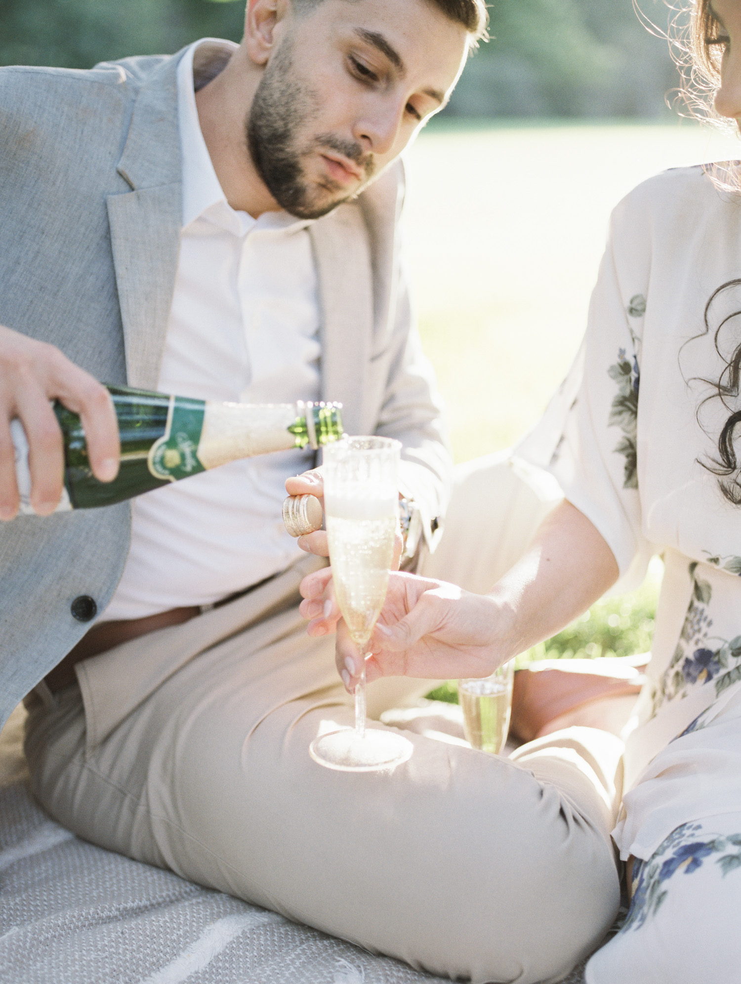 A couple pours champagne during their film engagement photos at the Ford House in Michigan
