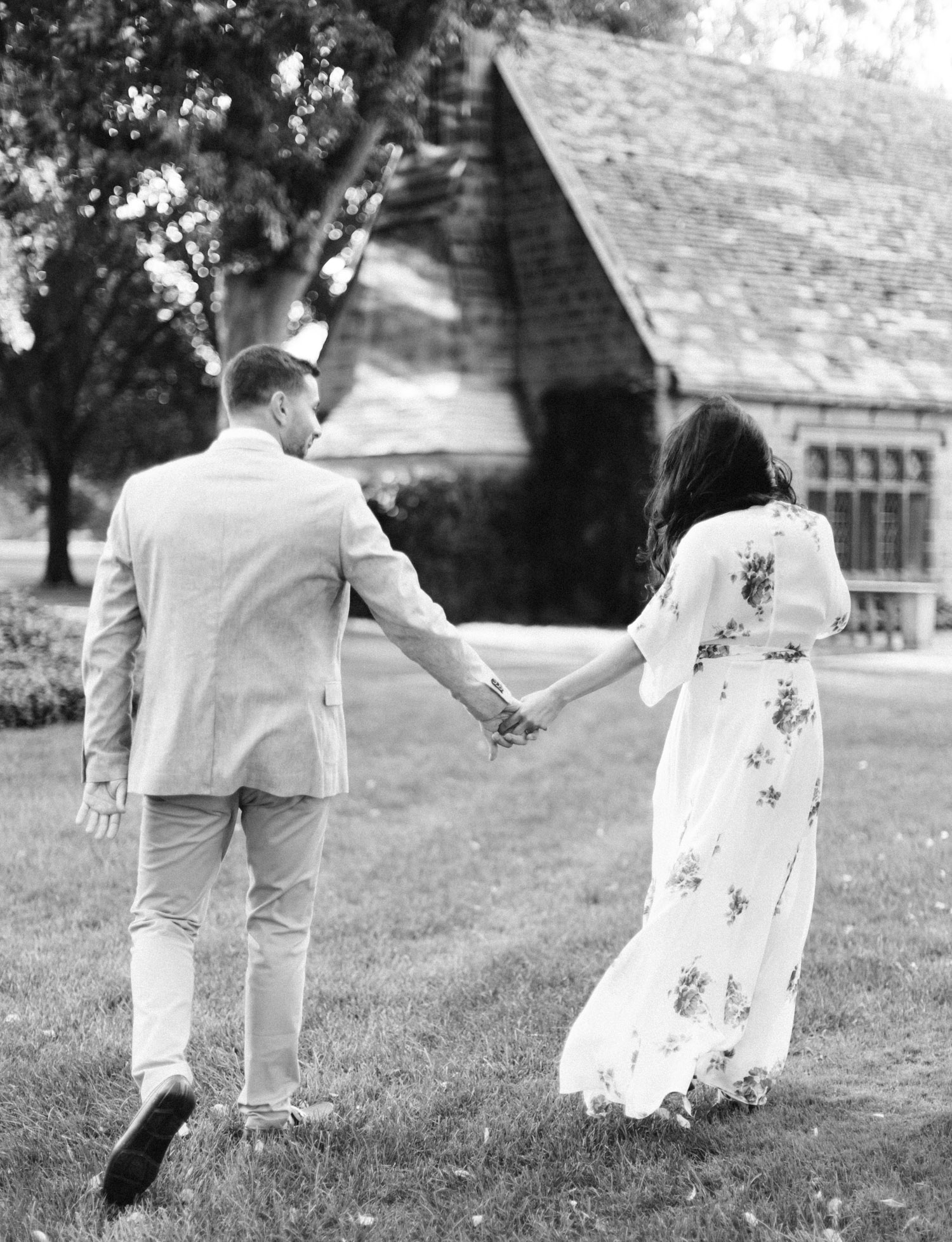 A dressed-up couple holds hands while walking toward the Ford House during their engagement photos