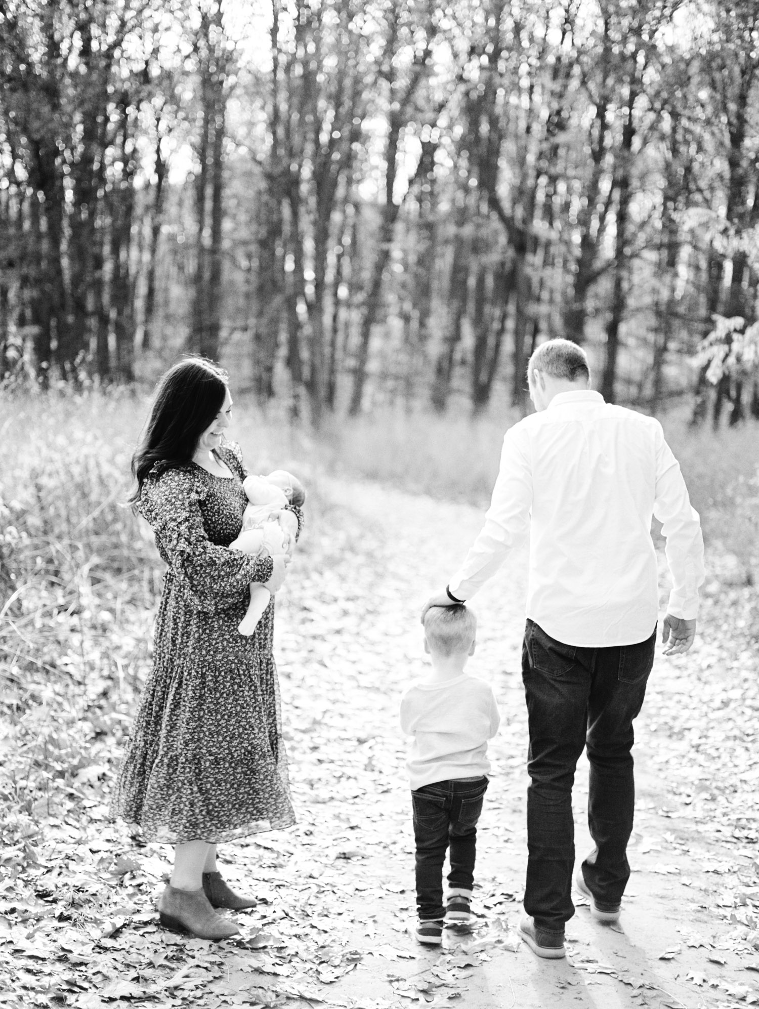 A family walks down a path together during their natural lifestyle film photos in Ann Arbor, Michigan