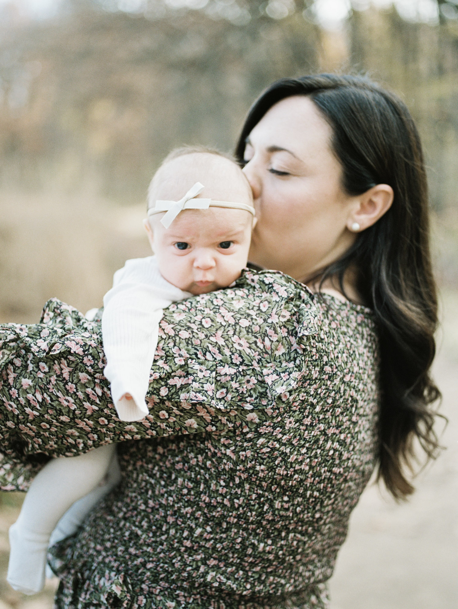 A mother kisses her newborn baby girl during fall family photos on film in Ann Arbor, Michigan