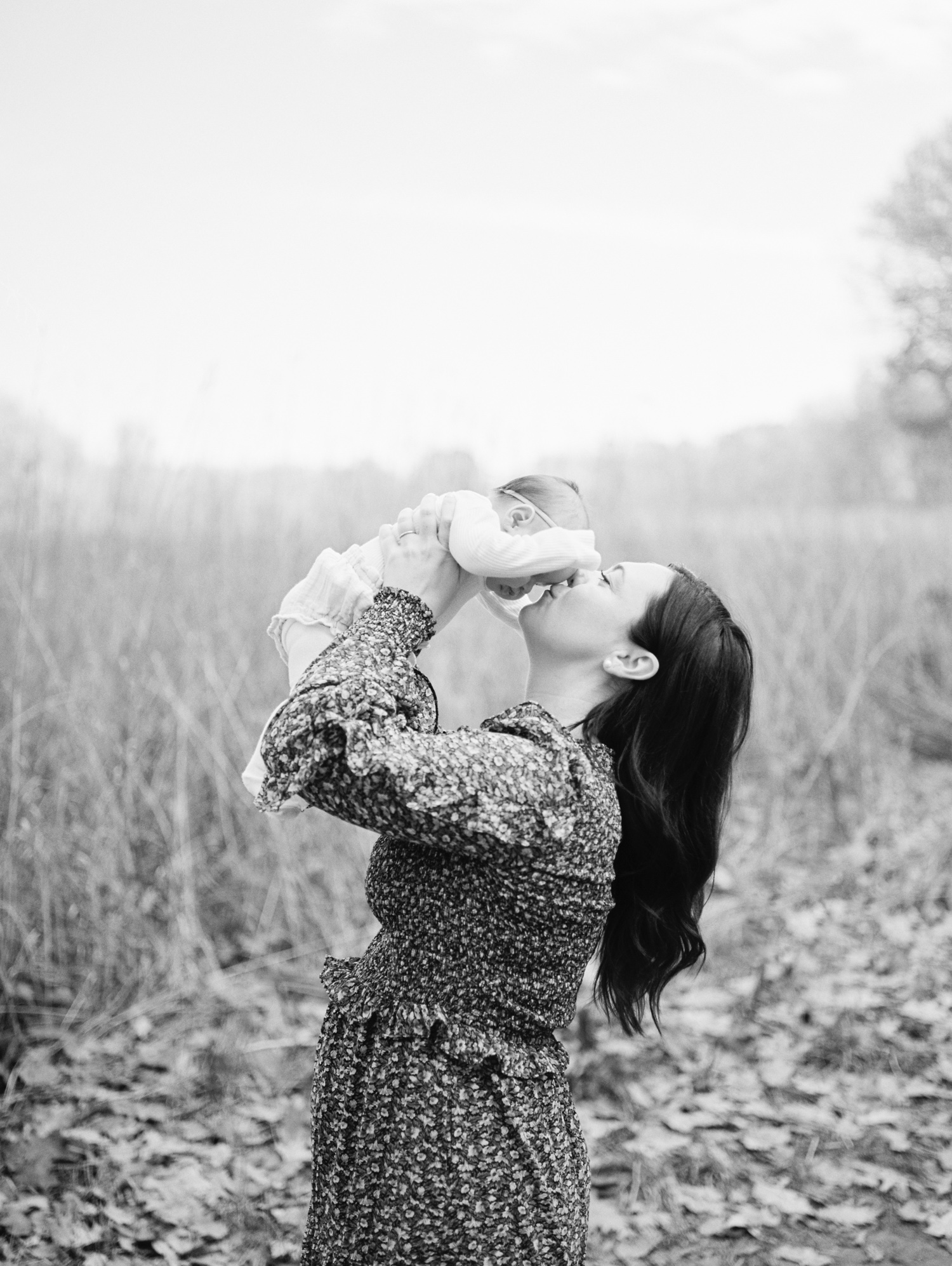 A mother holds and kisses her baby girl in an open field during film family photography near Ann Arbor, Michigan