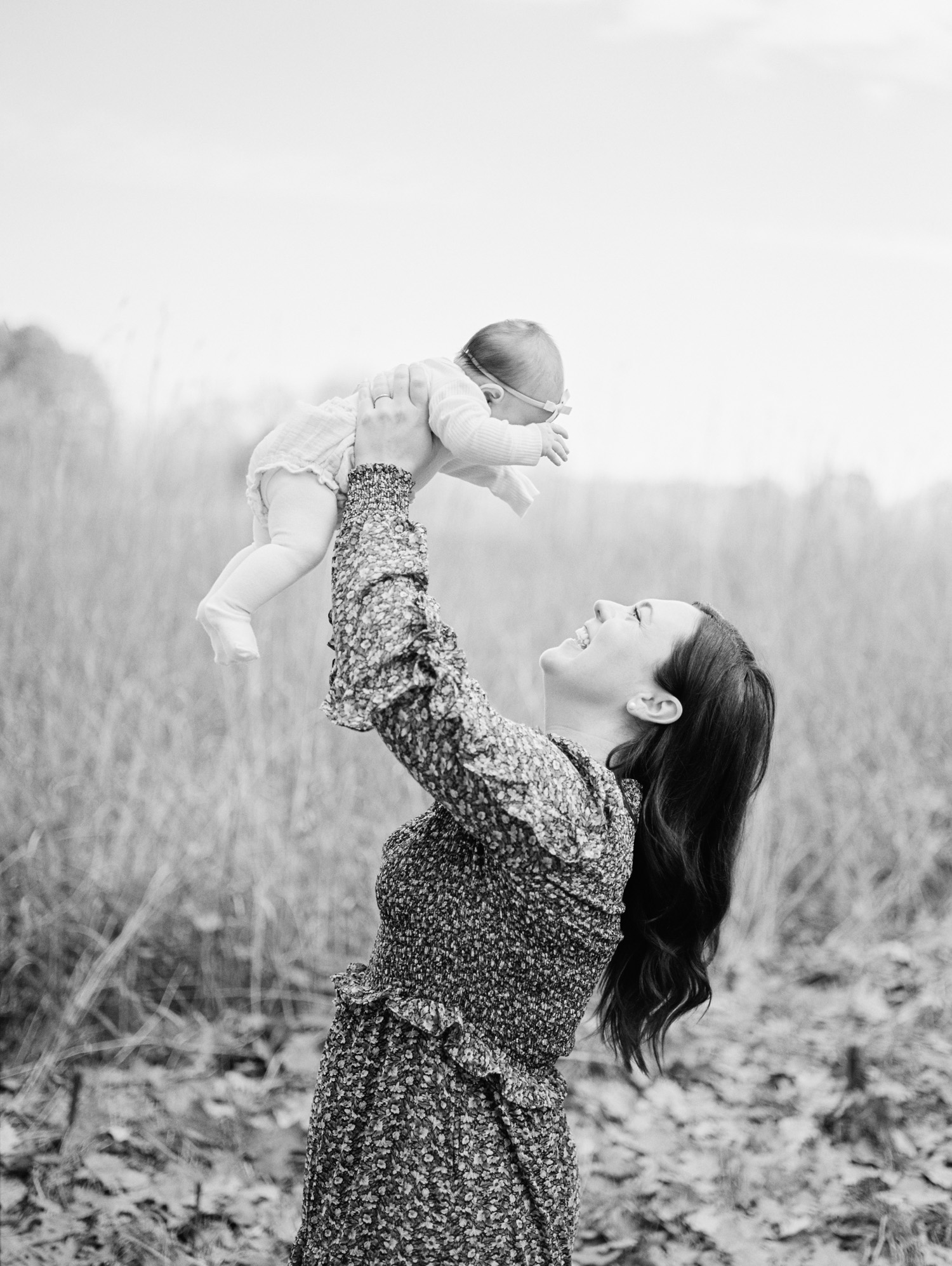 A mother in a floral dress holds her newborn baby daughter up in the air in a field in Ann Arbor, Michigan