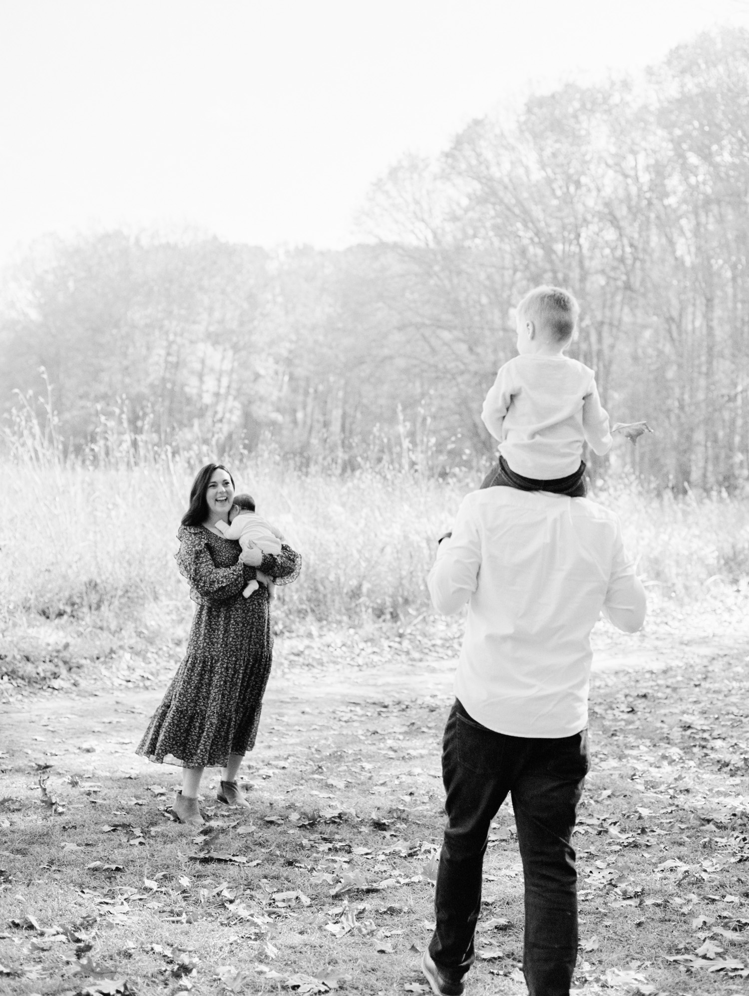 A mother holding her newborn daughter smiles at her young son as he rides on his father's shoulders during their natural, lifestyle family photography session in Ann Arbor, Michigan