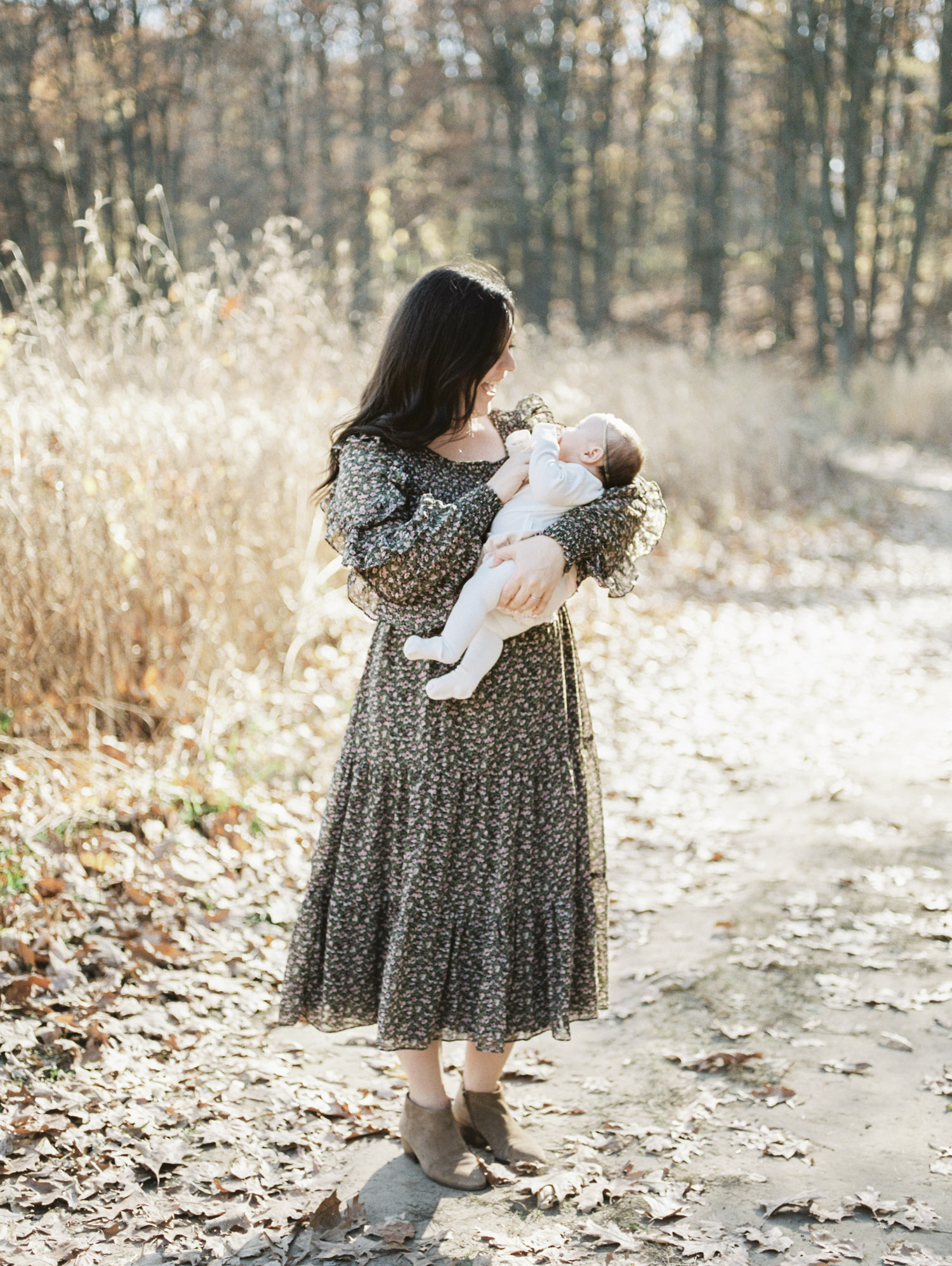 A mother in a brown floral dress holds her newborn daughter during their fall family photos in Ann Arbor, Michigan