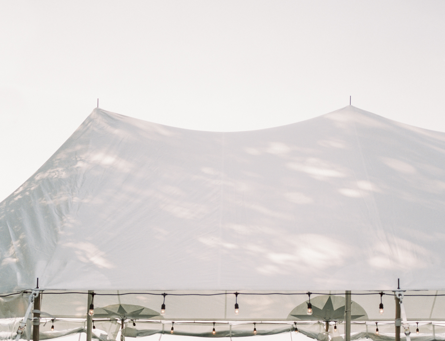dappled light is scattered across a sailcloth tent, captured on film during a Northern Michigan wedding