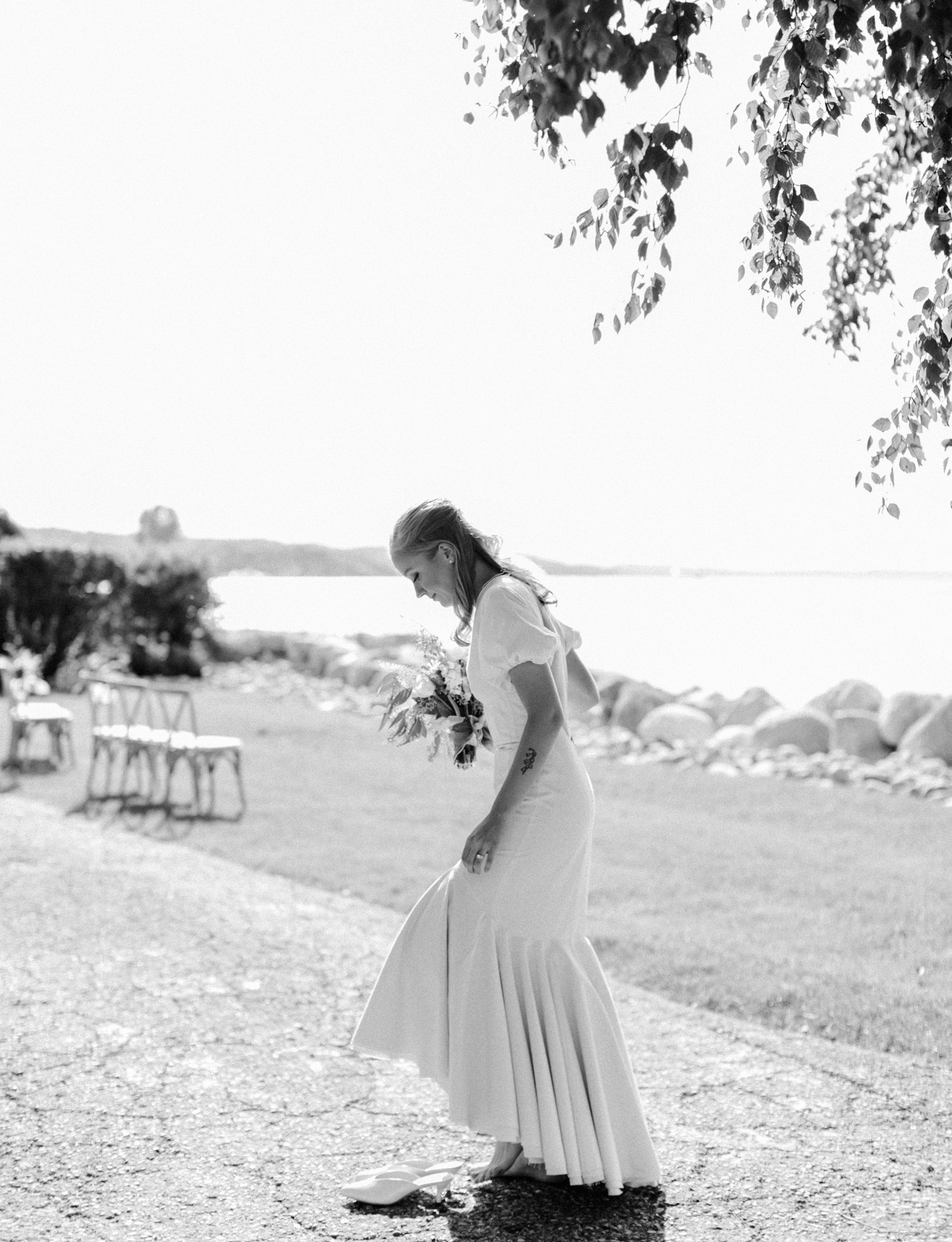 A barefoot bride in a vintage gown steps back into her shoes on the coast of Lake Michigan
