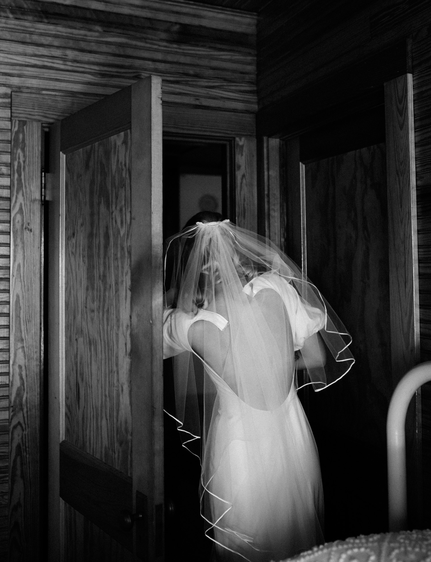 The back of a bride's vintage wedding dress is undone as she peeks through a doorway to ask her mother's help