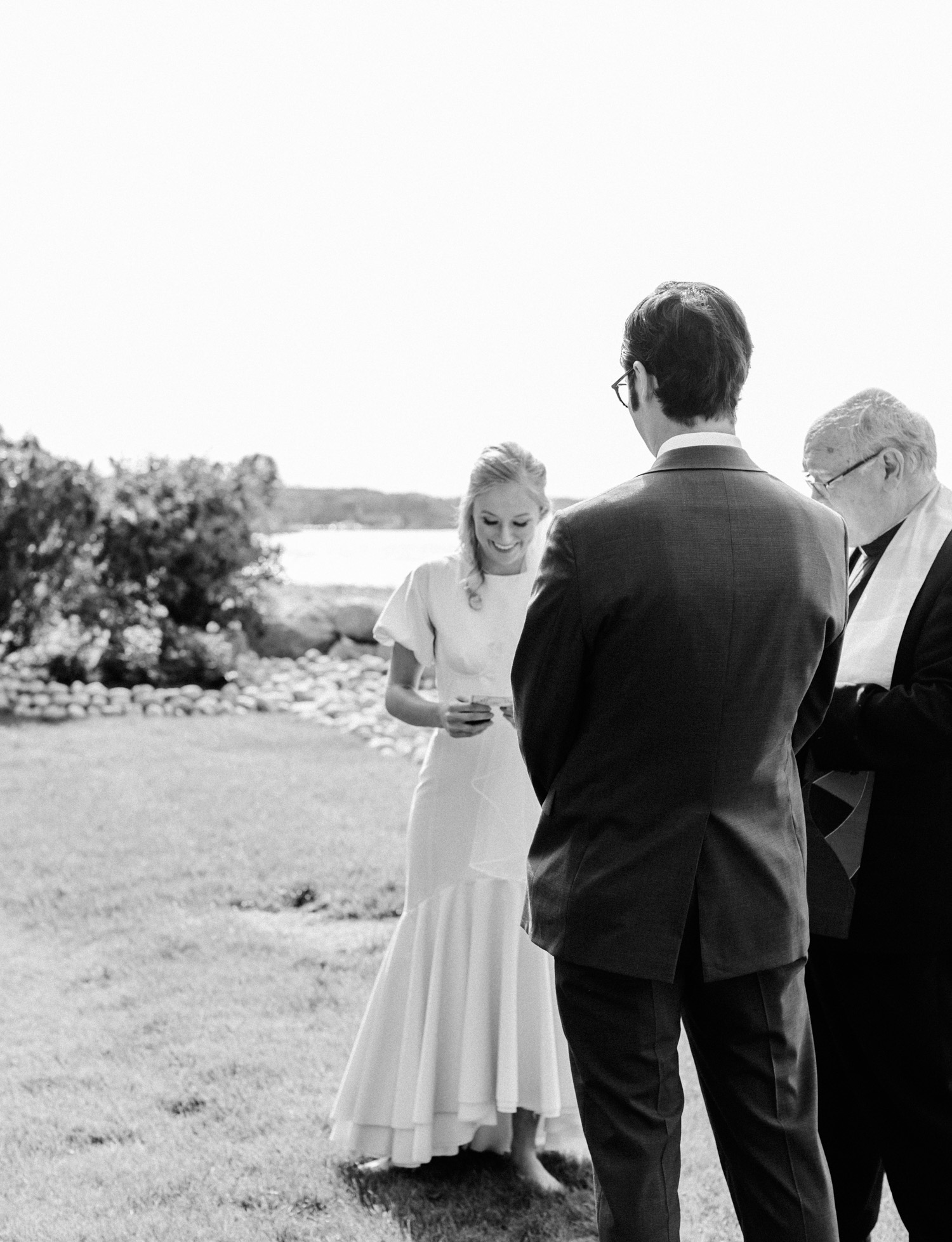 A bride smiles while reading her vows during her wedding ceremony on lake Michigan