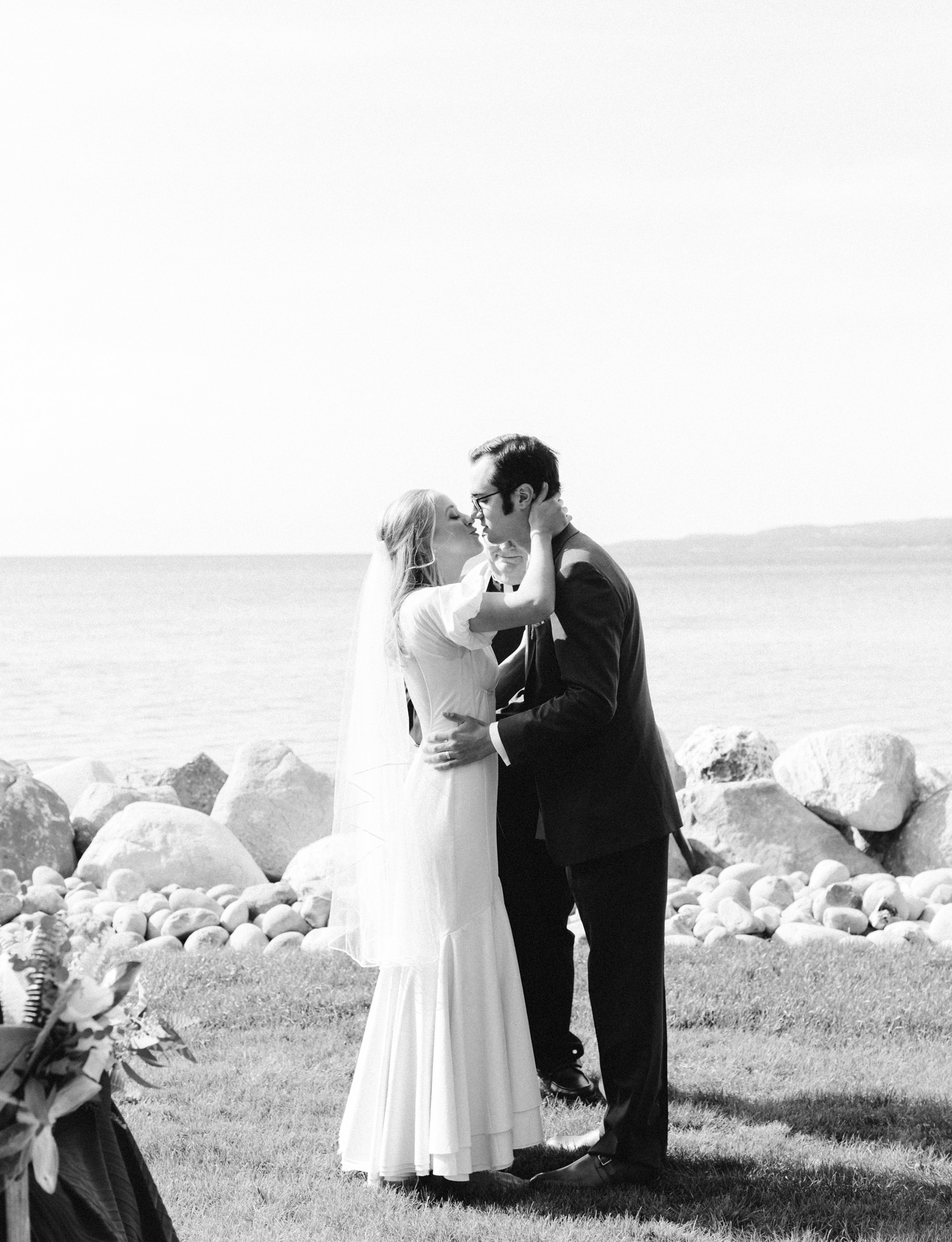A bride and groom share their first kiss in black and white during their Lake Michigan wedding ceremony in Petoskey