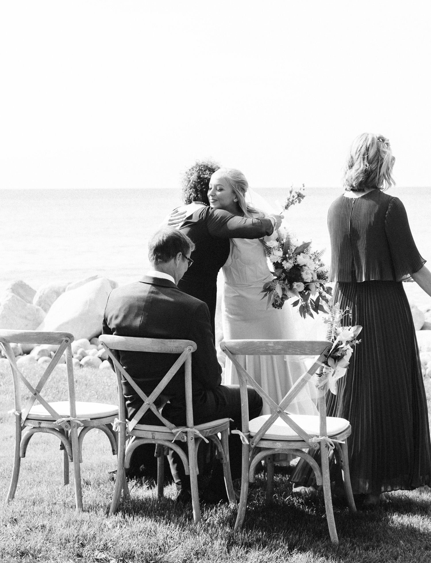 A bride hugs her mother-in-law just after the wedding ceremony on Lake Michigan in Petoskey