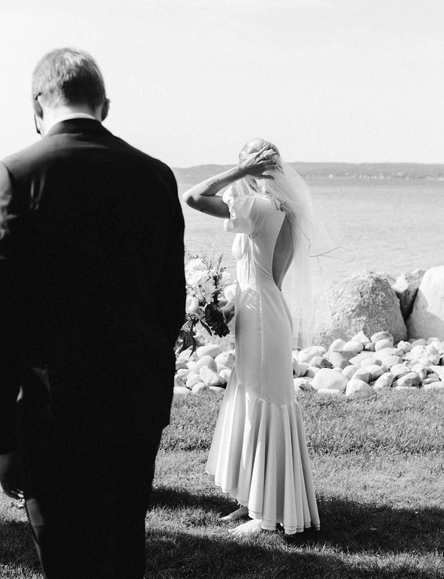 A bride in a vintage inspired gown adjusts her veil during her Lake Michigan wedding in Petoskey