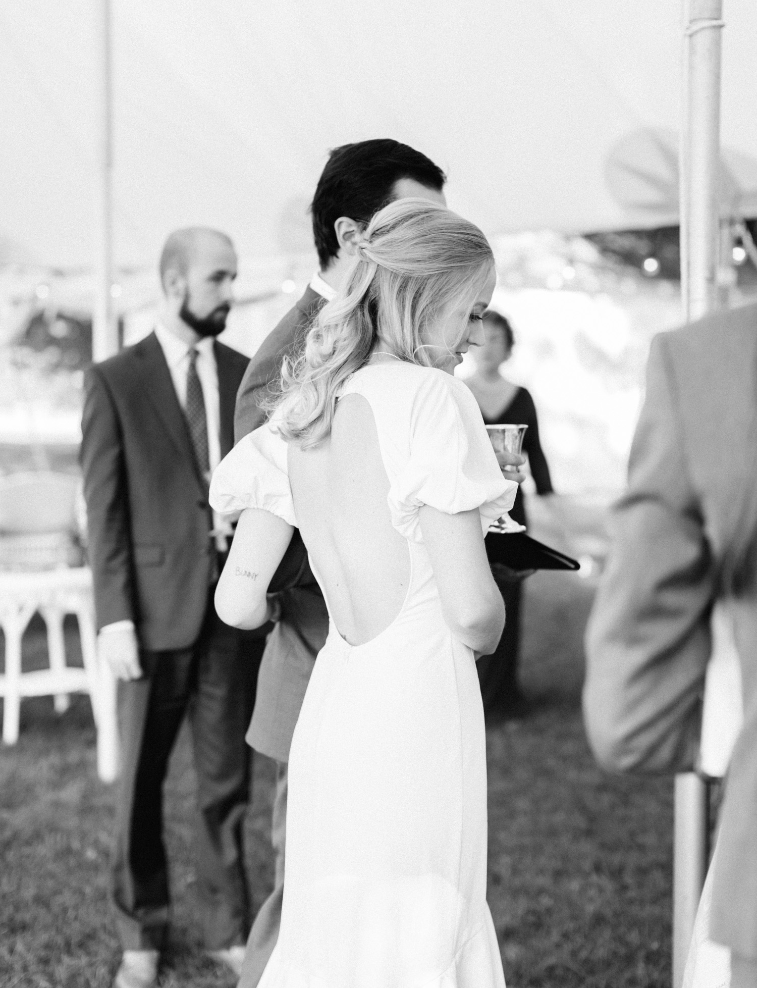A bride in a vintage gown holds her groom's arm during their intimate wedding up north