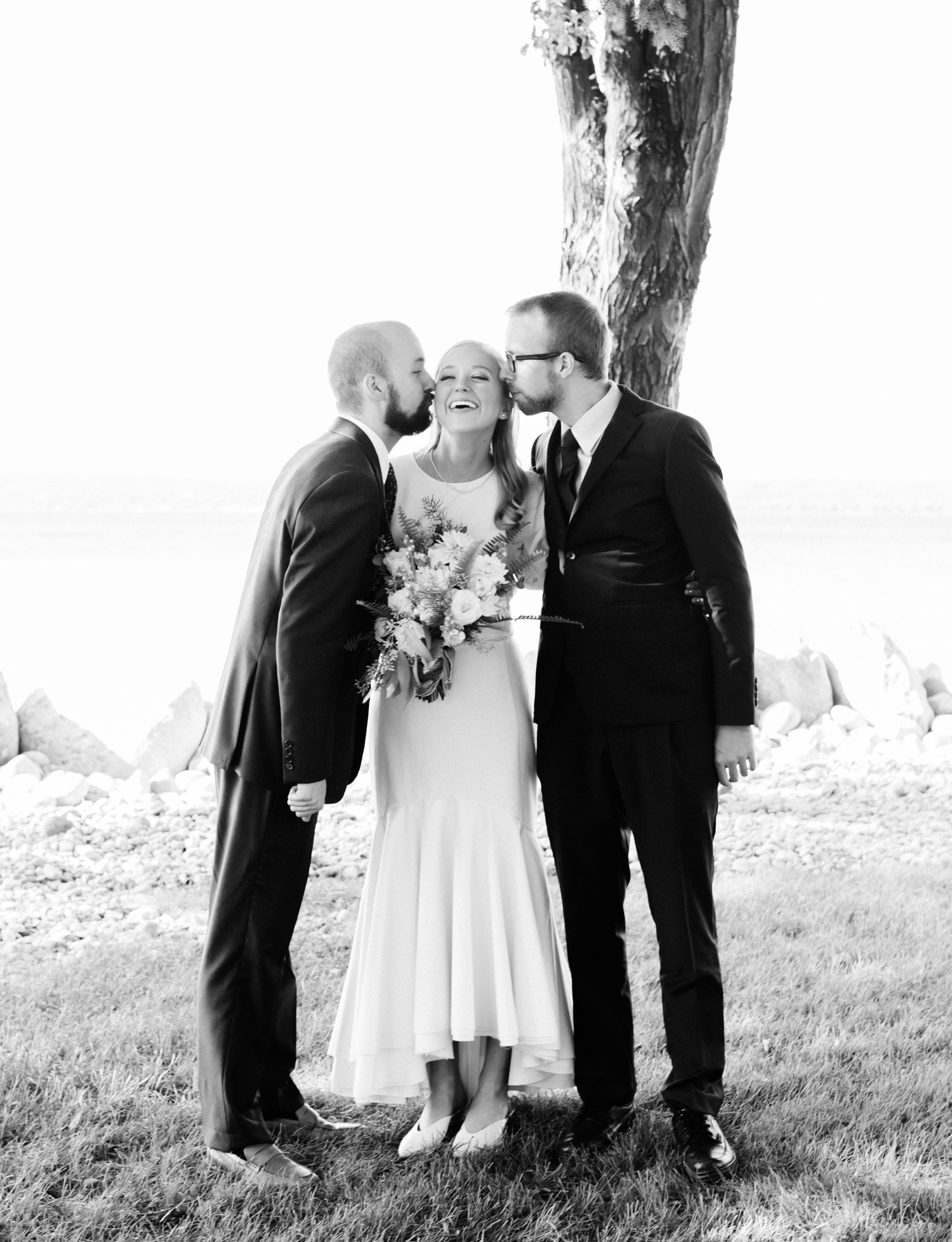 A bride receives kisses on the cheek from both her brothers during her Petoskey, Michigan wedding