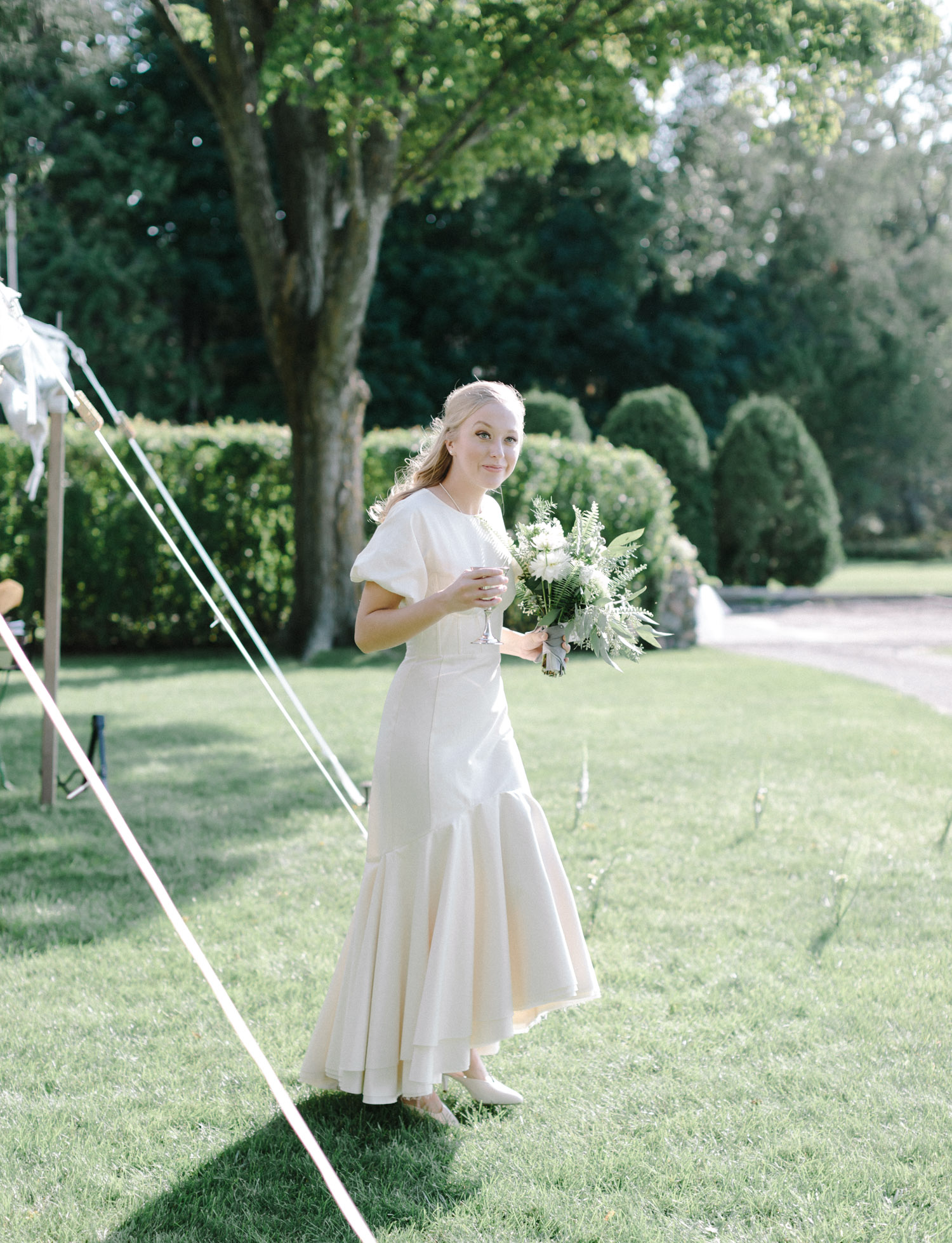 A bride with vintage style walks under a sailcloth tent in Northern Michigan