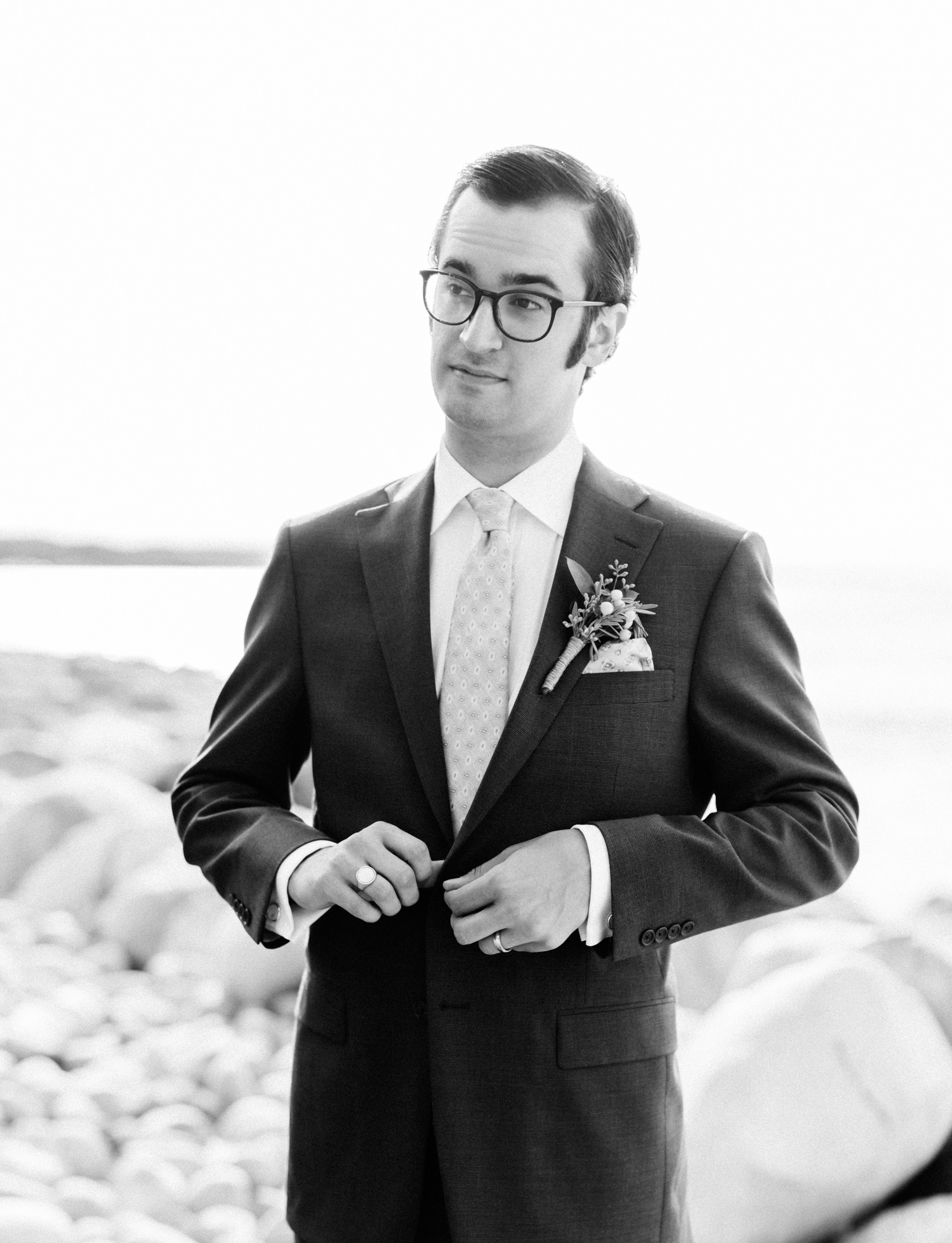 A groom with 70's style buttons his jacket before seeing his bride during their Northern Michigan wedding