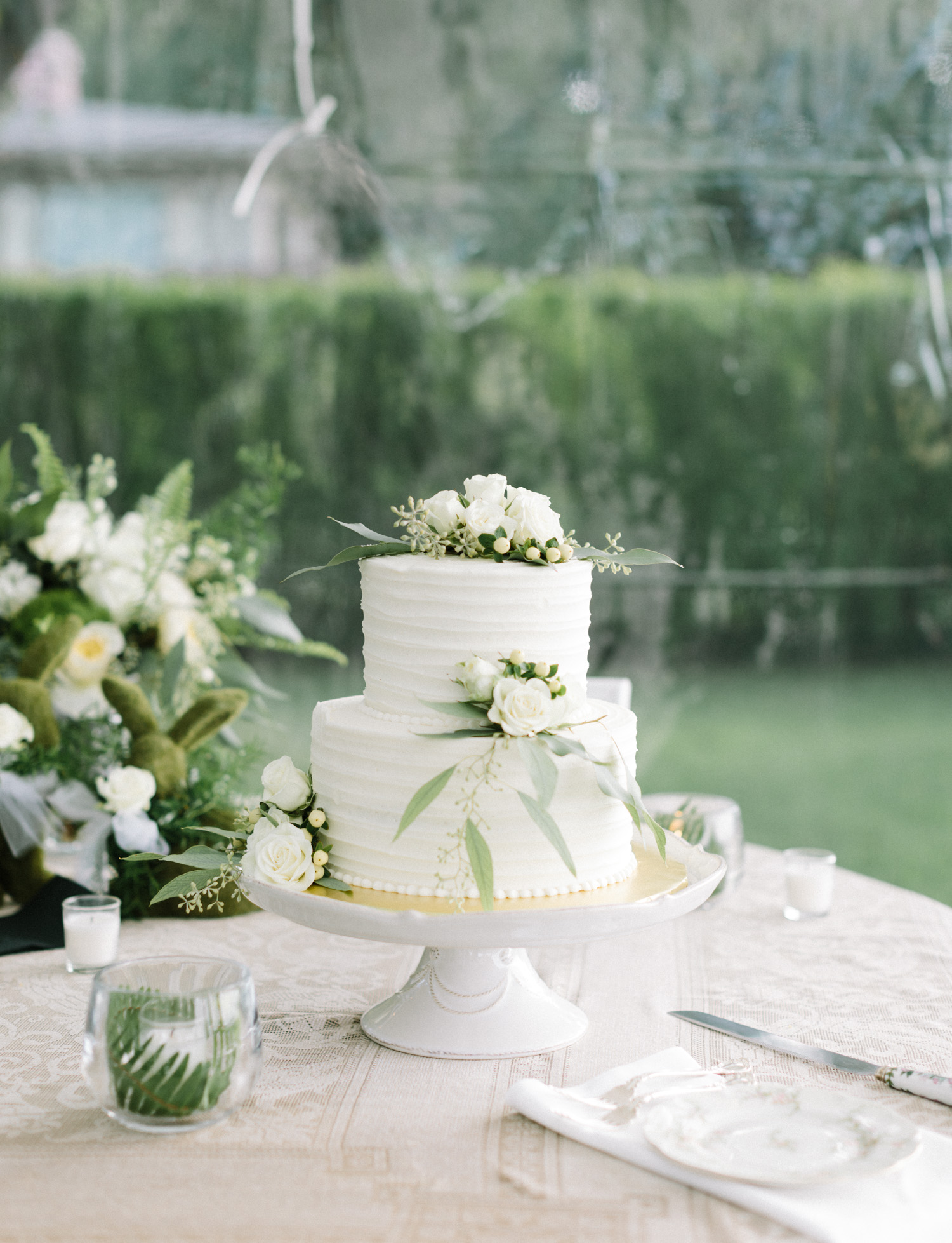 A vanilla iced wedding cake with flowers and greenery in Petoskey, northern Michigan