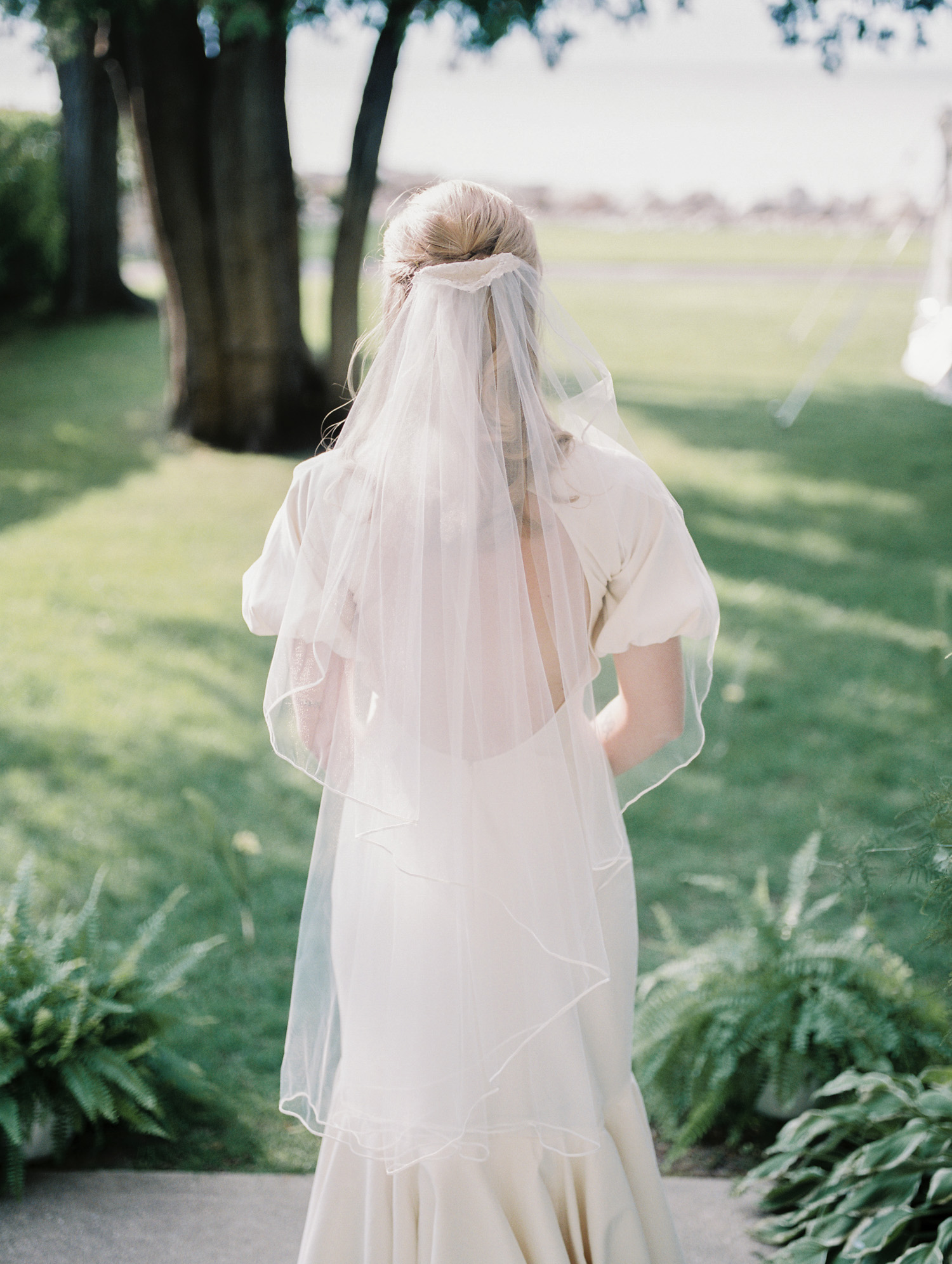 A bride in a fingertip length veil with the vintage sentimental detail of her grandmother's wedding dress in Petoskey, Michigan