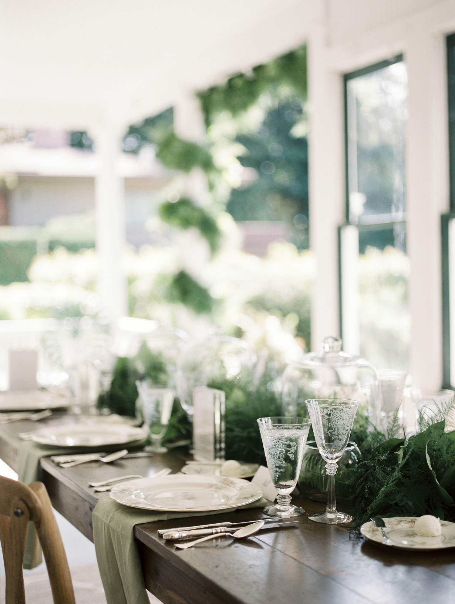 An intimate wedding dinner table with greenery and vintage glassware in Petoskey, Michigan