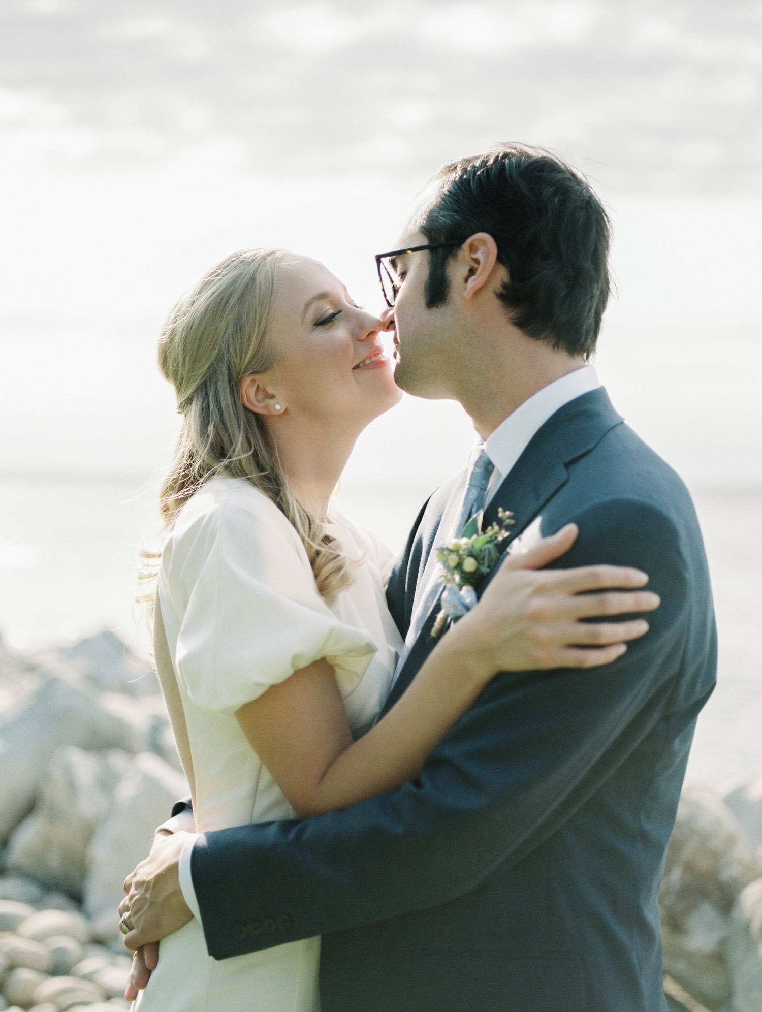 A bride leans in to kiss her groom in front of Lake Michigan during their Petoskey wedding