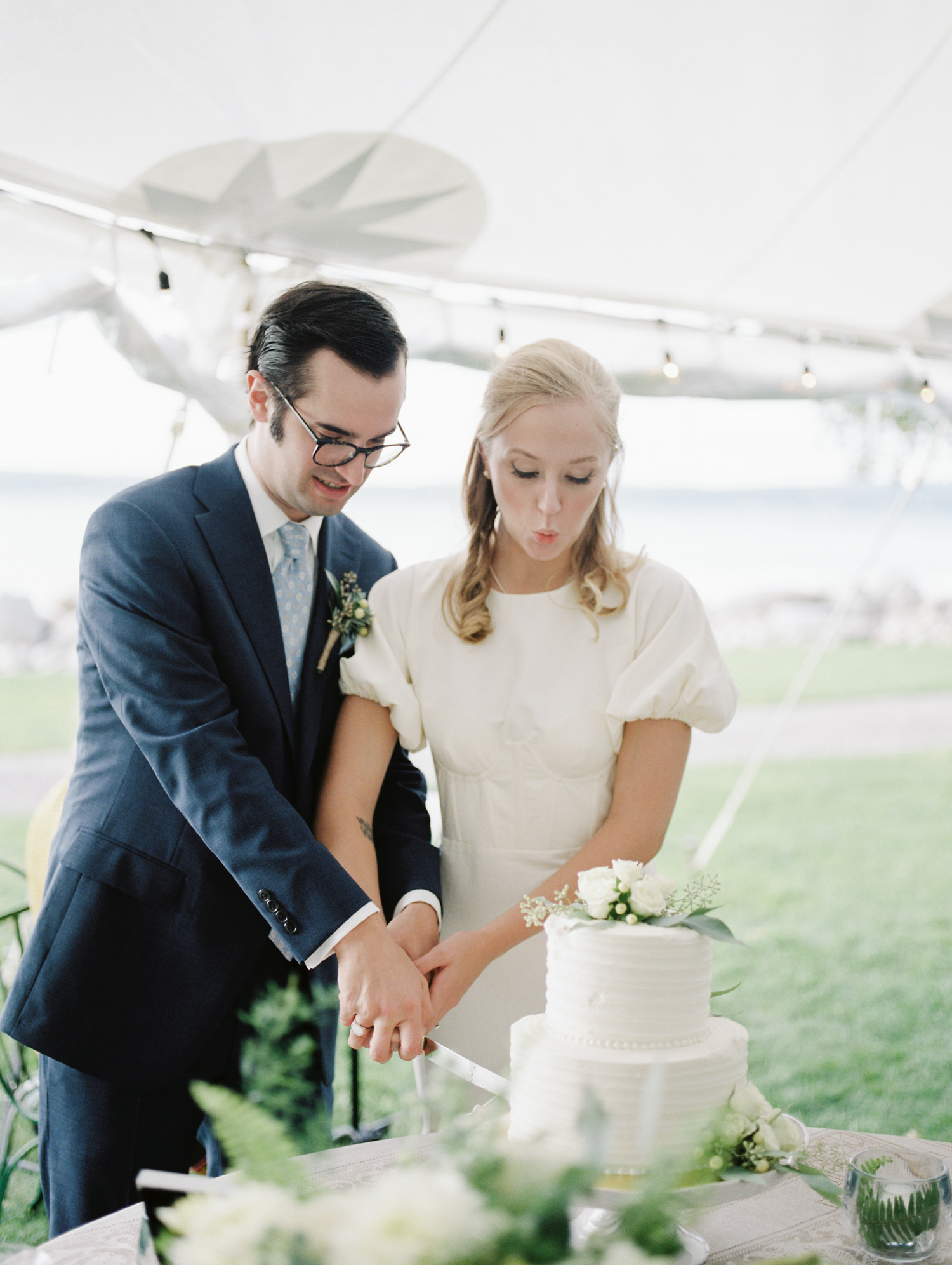 a stylish couple cuts their wedding cake under a sailcloth tent in Petoskey, Northern Michigan