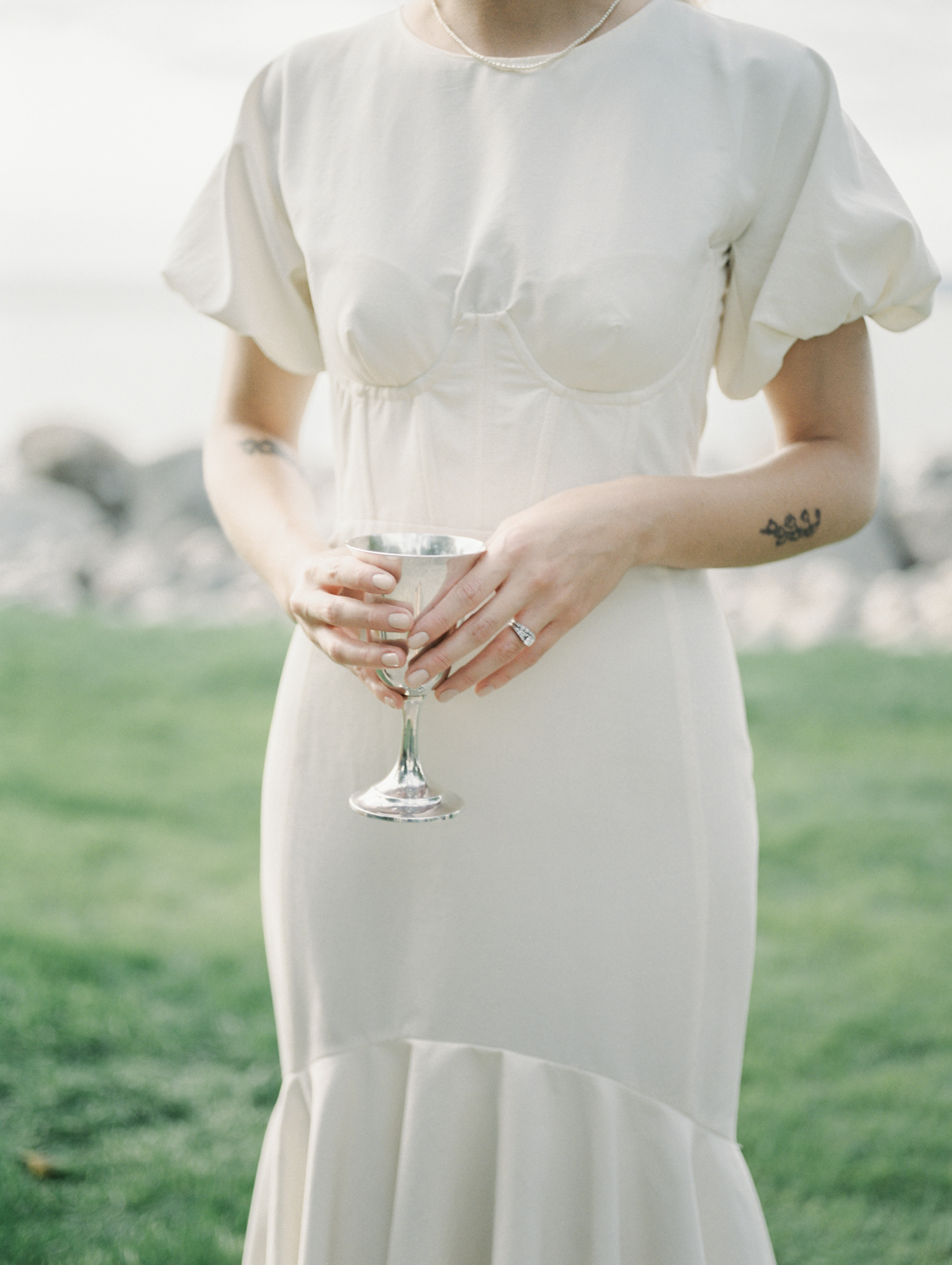 A bride with tattoos and a vintage wedding gown holds a silver cup during her Lake Michigan wedding in Petoskey