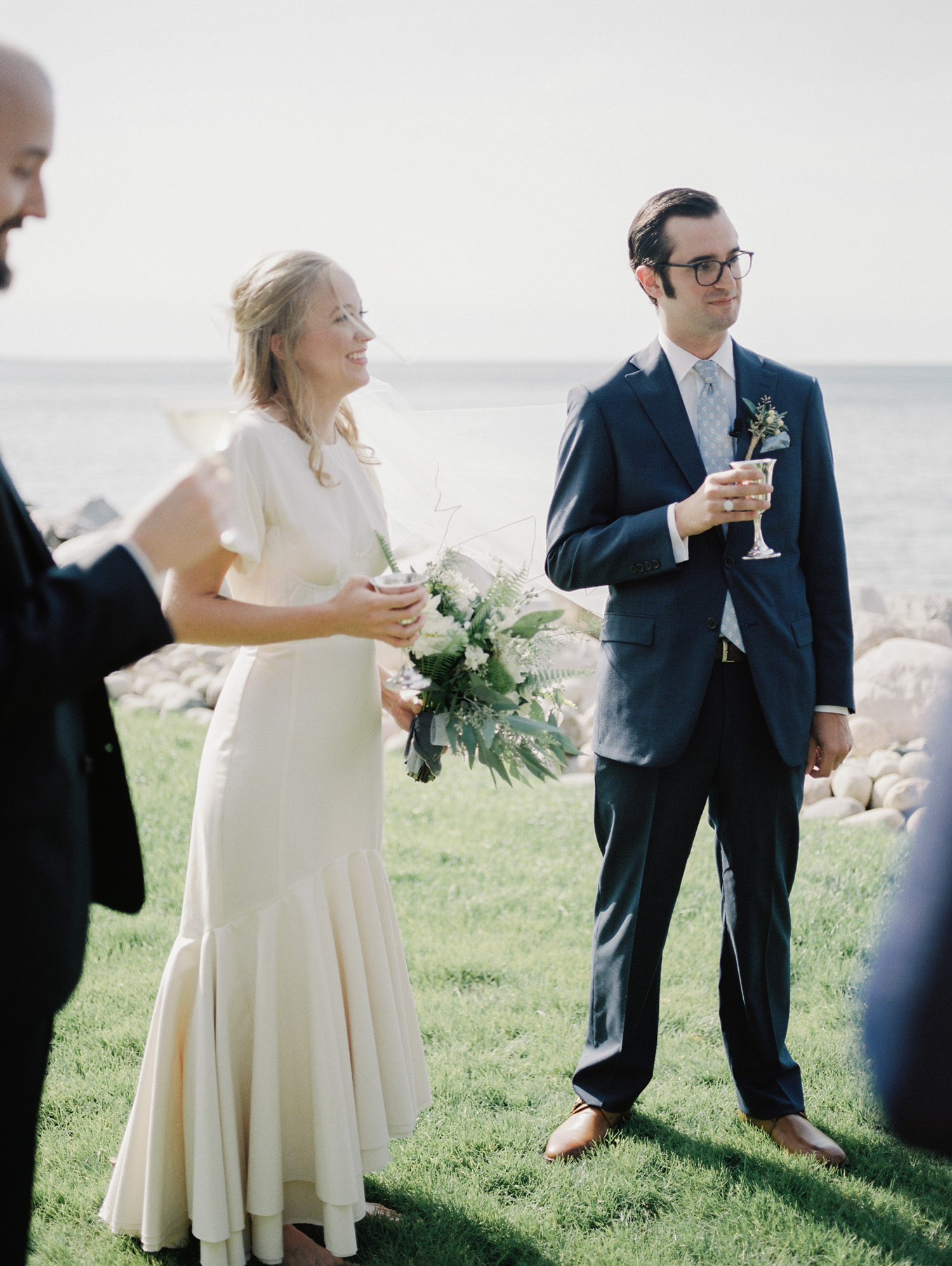 A newlywed couple toasts with silver goblets after their wedding ceremony on lake Michigan