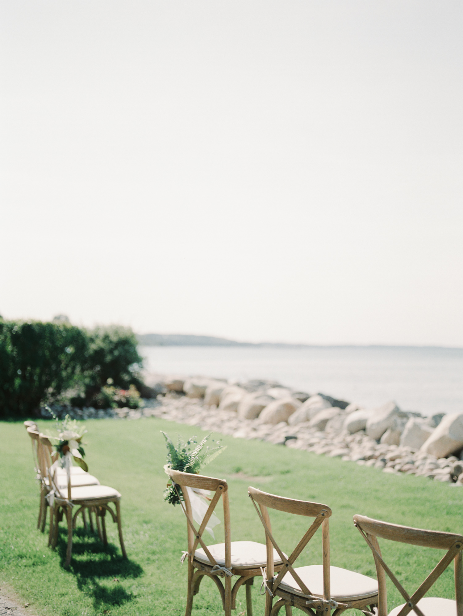 An intimate, small wedding ceremony setup with wood chairs on Lake Michigan in Petoskey