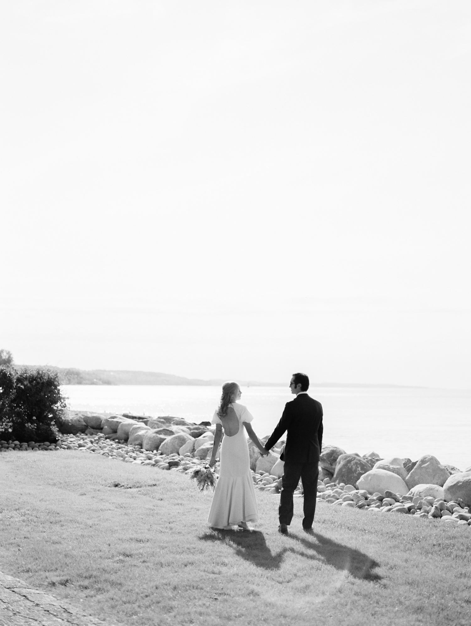 A bride and groom walk hand in hand toward Lake Michigan in Petoskey