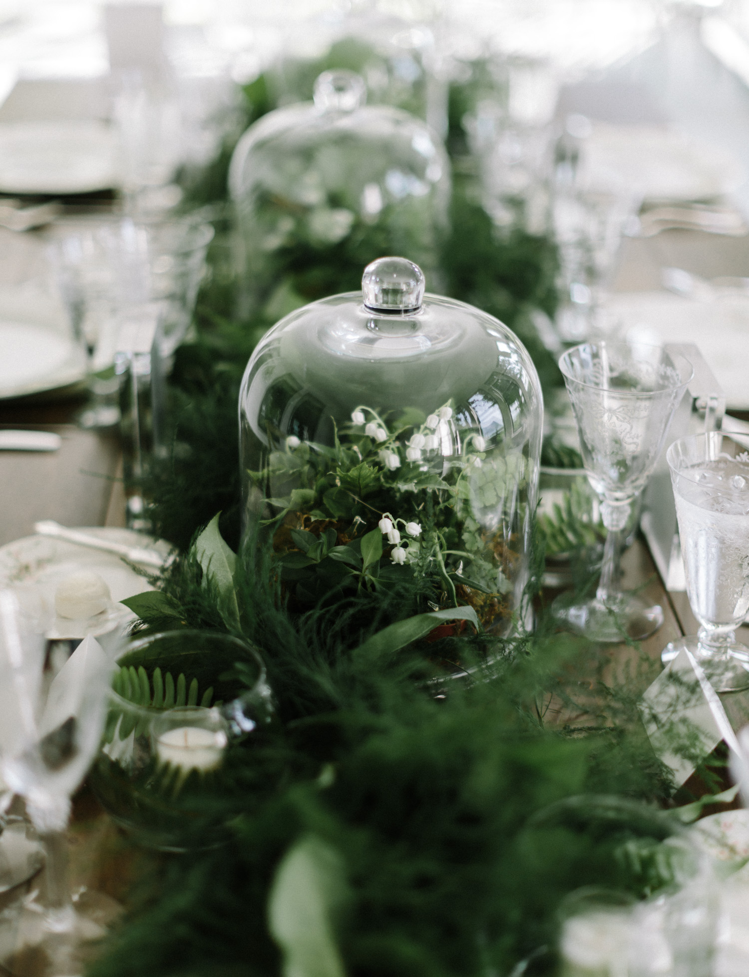 Cloche centerpieces with lush greenery and lily of the valley rest on a dinner table in Petoskey, Michigan