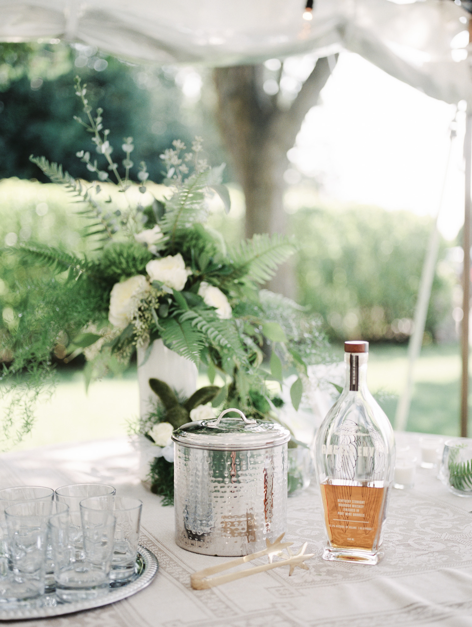 A floral arrangement with greenery and ferns rests on a table with a bottle of whiskey in Northern Michigan