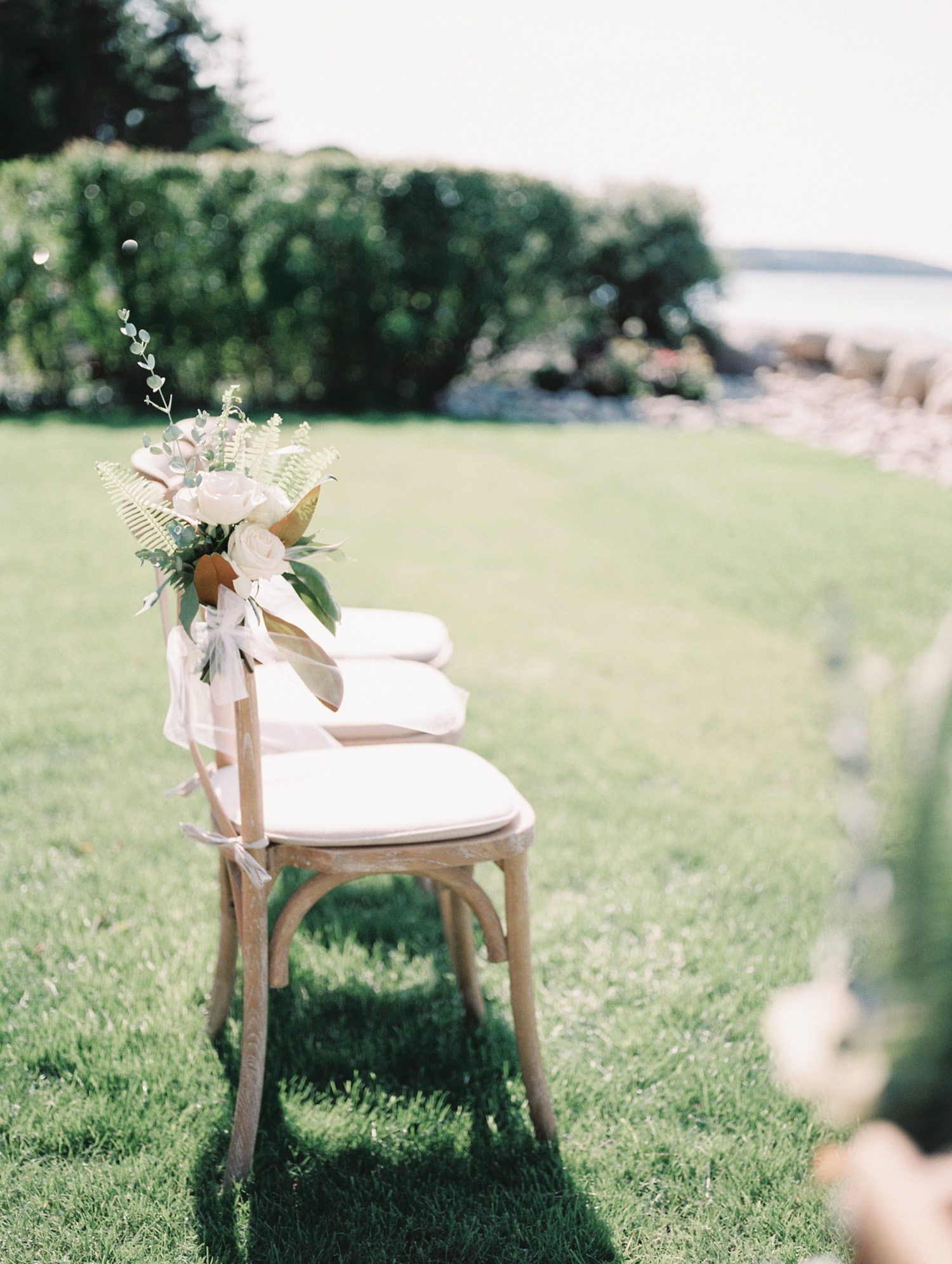wood wedding ceremony chairs with flowers on the coast of Lake Michigan in Petoskey