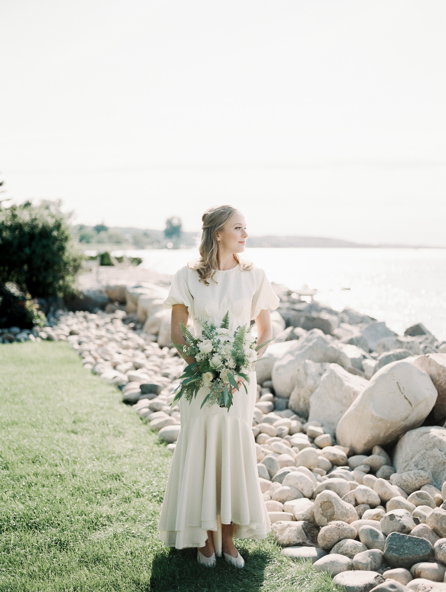 A blonde bride in a vintage inspired gown looks out at Lake Michigan in Petoskey