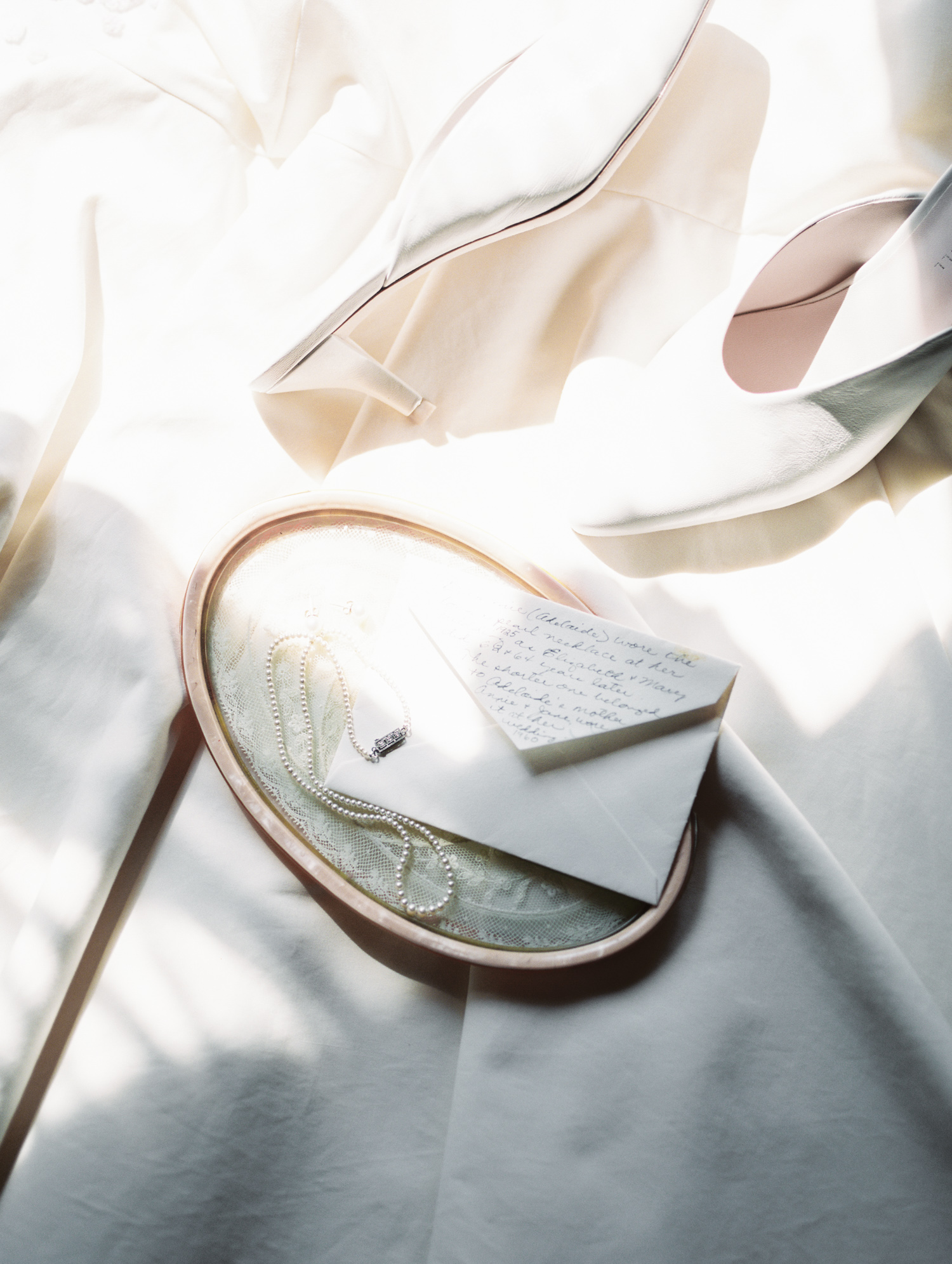 an antique pearl necklace, handwritten letter, and wedding shoes are heirloom wedding details captured on film during a Petoskey, Michigan wedding