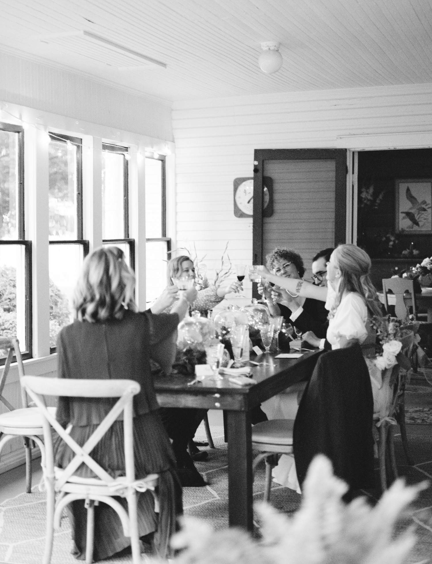 wedding guests toast with glasses during an intimate small wedding dinner in Petoskey