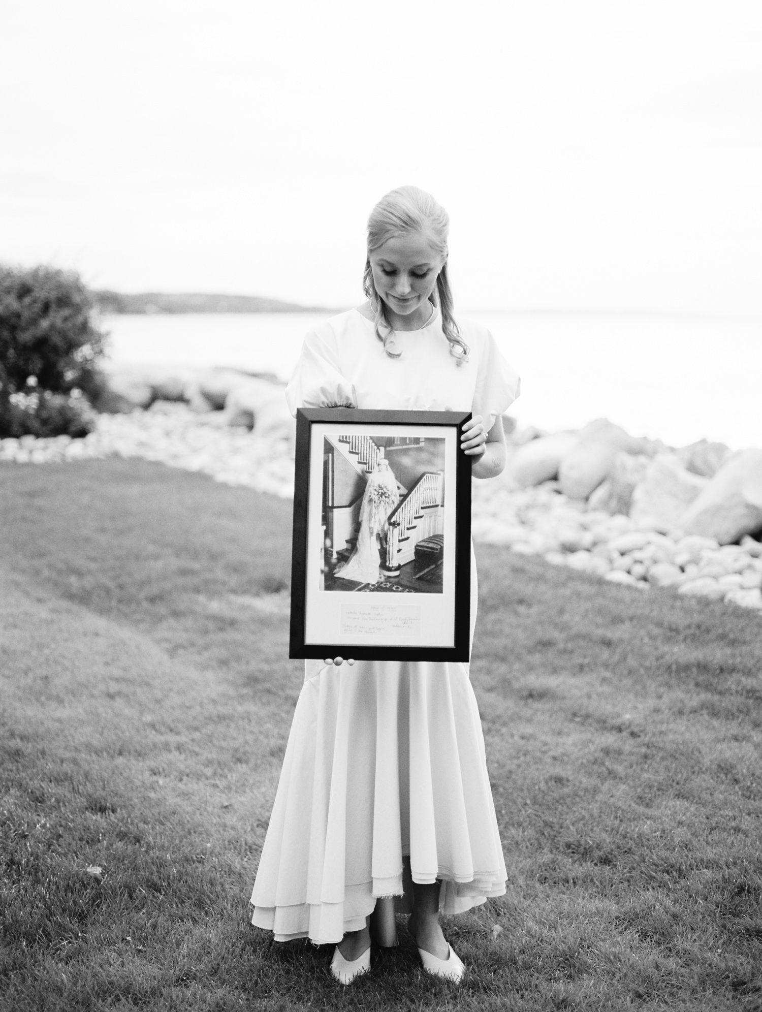 on Lake Michigan, a bride holds a photo of her grandmother on her wedding day in Petoskey