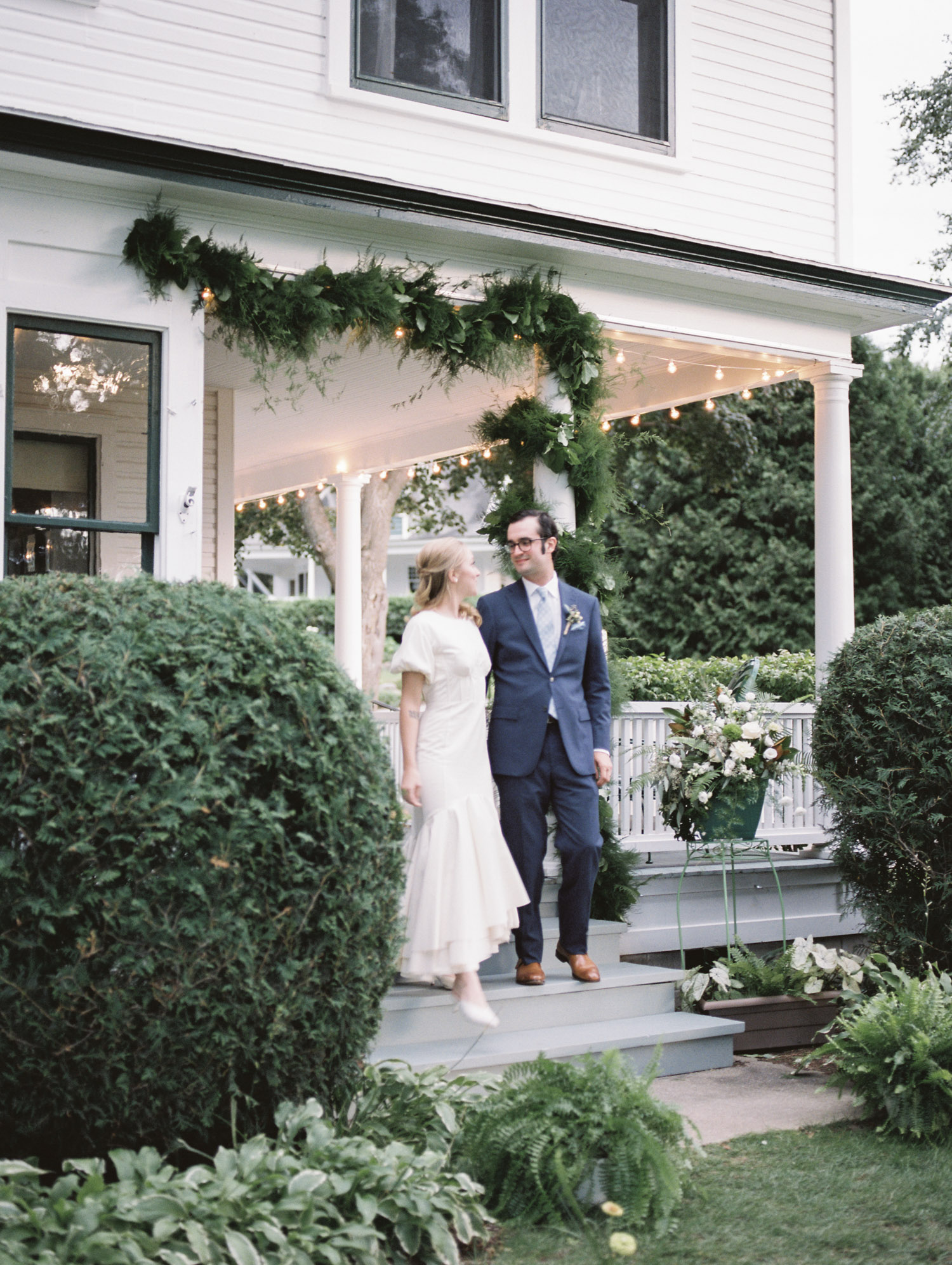 A bride and groom walk together under a greenery garland during their Petoskey, Michigan wedding